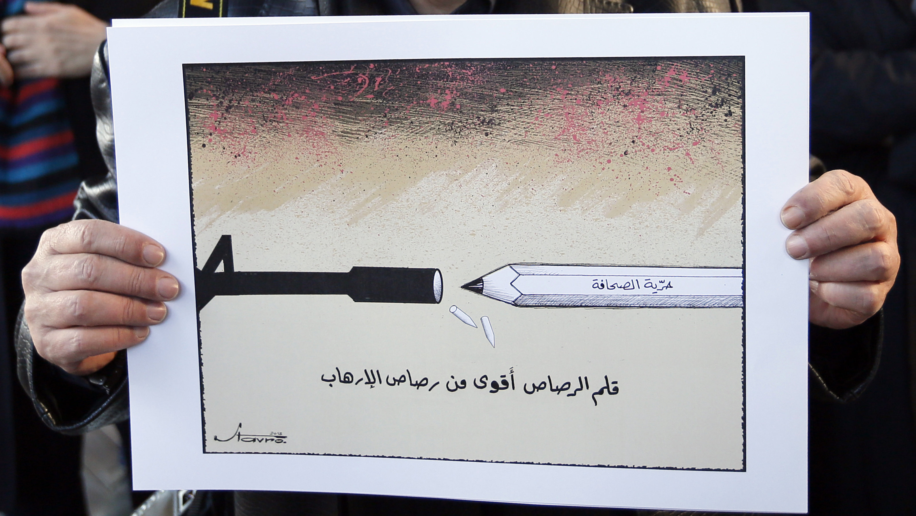 "Caricaturist Stavro Jabra holds up his cartoon during a rally held in solidarity with the victims of a shooting by gunmen at the Paris offices of the satirical weekly newspaper Charlie Hebdo earlier this week, in Beirut January 11, 2015. The words on the cartoon read, ""Pencil lead is stronger than terrorism""."