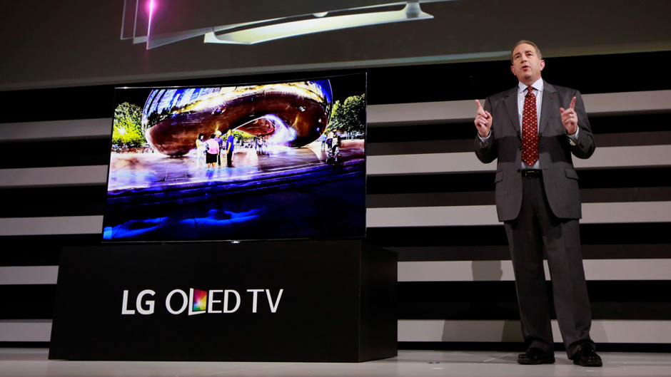 """Tim Alessi, director of new product development at LG Electronics USA, unveils LG's new 77"""" Flexible 4K OLED TV during a news conference at the 2015 International CES on Monday, Jan. 5, 2015, in Las Vegas. (Photo by Jack Dempsey/Invision for LG/AP Images)"""