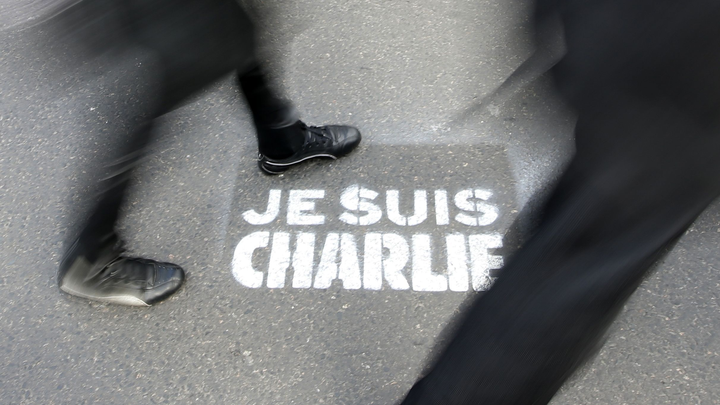 """People walk past a grafitti tag reading """"I am Charlie"""" as they take part in a solidarity march (Marche Republicaine) in the streets of Paris January 11, 2015. French citizens will be joined by dozens of foreign leaders, among them Arab and Muslim representatives, in a march on Sunday in an unprecedented tribute to this week's victims following the shootings by gunmen at the offices of the satirical weekly newspaper Charlie Hebdo, the killing of a police woman in Montrouge, and the hostage taking at a kosher supermarket at the Porte de Vincennes. REUTERS/Eric Gaillard (FRANCE - Tags: CRIME LAW POLITICS CIVIL UNREST SOCIETY TPX IMAGES OF THE DAY) - RTR4KXO7"""