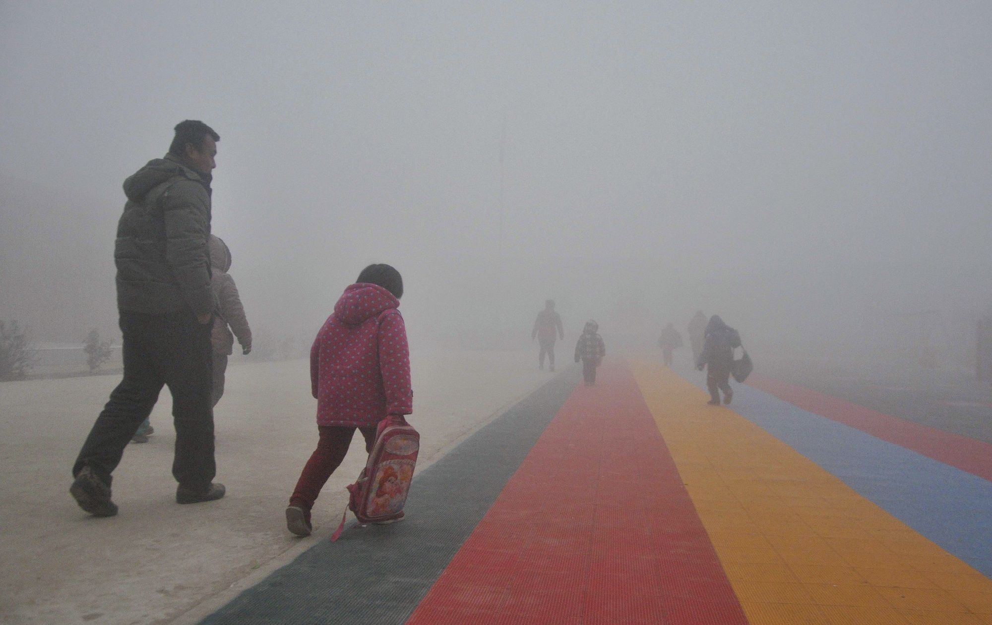 Parents walk primary school students to school amid thick haze in Chiping county, Shandong province