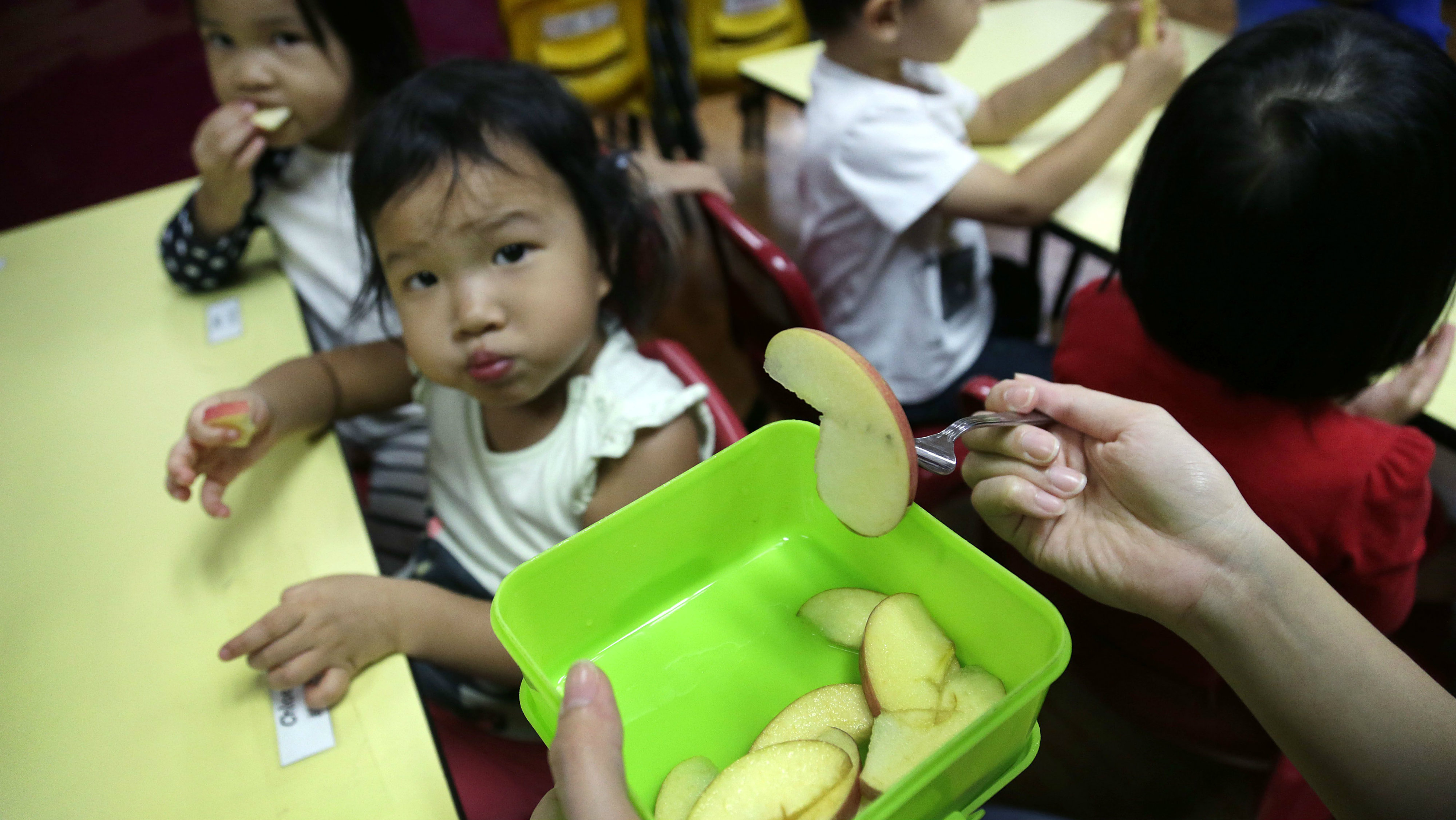 A teacher gives out apples as snacks ahead of lunch, Tuesday, May 6, 2014 at Delcare Edu Center, a local kindergarten and child care center in the business district of Singapore. Everyday, lunch is prepared by the school kitchen staff and efforts to promote healthy eating in this particular center is seen in painstaking efforts in selection of their ingredients and food preparation methods. The children in this school are also taught to accept wide varieties of food and a weekly menu is planned by the principal for each school term. Healthy snacks consisting of fruits, home-made bread, natural beans, soup, and barley are served as their snacks between meals. (AP Photo/Wong Maye-E)