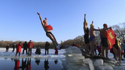 DATE IMPORTED:January 01, 2015A swimmer falls into the water after he stood on ice cubes, at subzero temperature in Shenyang, Liaoning province January 1, 2015. REUTERS/Stringer