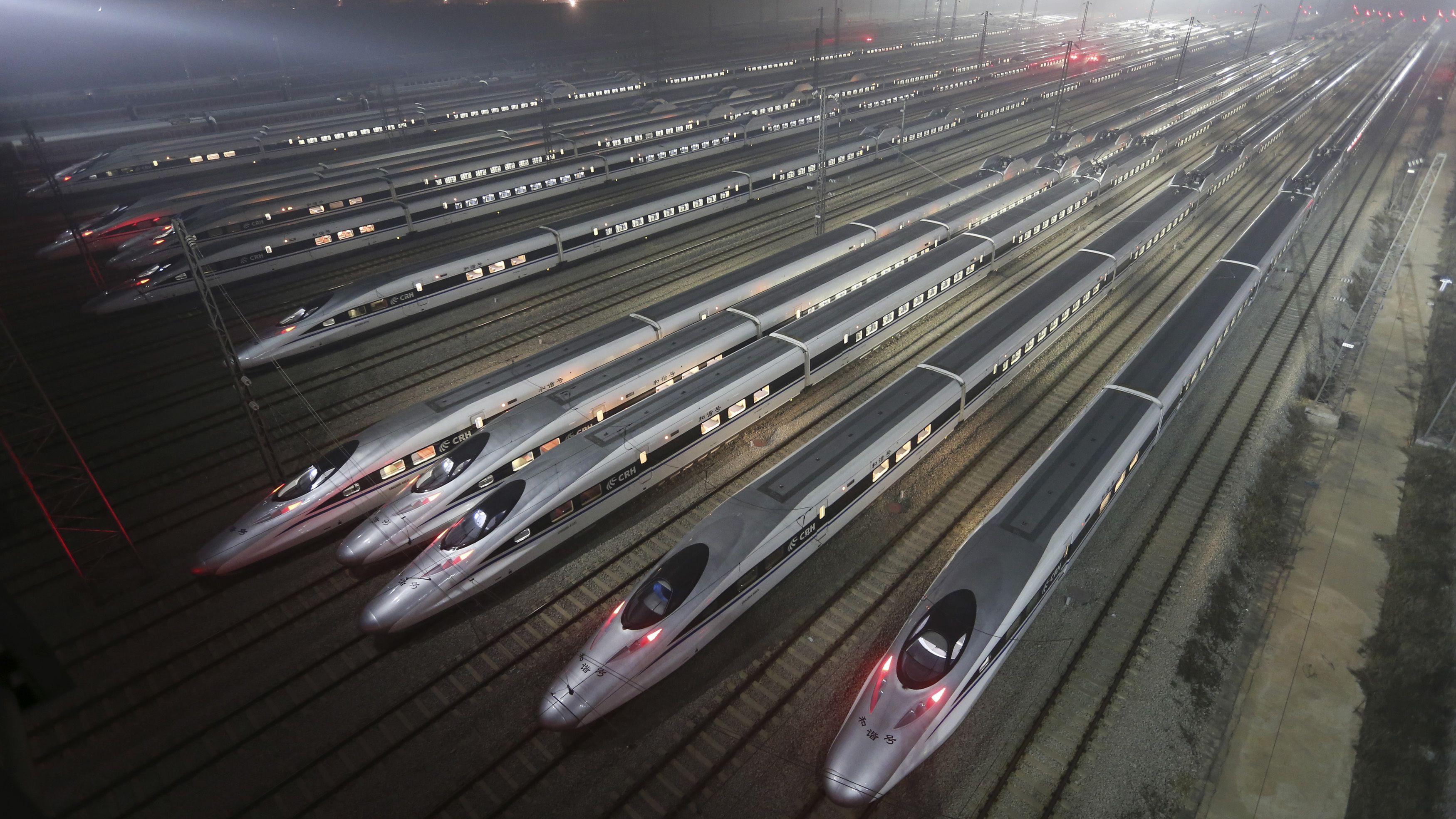 CRH380 (China Railway High-speed) Harmony bullet trains are seen at a high-speed train maintenance base in Wuhan, Hubei province, early December 25, 2012. China will open the world's longest high-speed rail line this week when a link between Beijing and the southern metropolis of Guangzhou is inaugurated, officials said on Saturday, underscoring its commitment to a trouble-plagued transport scheme. Rail investment slowed sharply in the wake of that accident and state media reported earlier this year that the government had cut planned railway investment by 500 billion yuan ($80.27 billion) to 2.3 trillion yuan under a five-year plan to 2015. REUTERS/Stringer (CHINA - Tags: TRANSPORT SOCIETY BUSINESS TPX IMAGES OF THE DAY) CHINA OUT. NO COMMERCIAL OR EDITORIAL SALES IN CHINA - RTR3BVZM