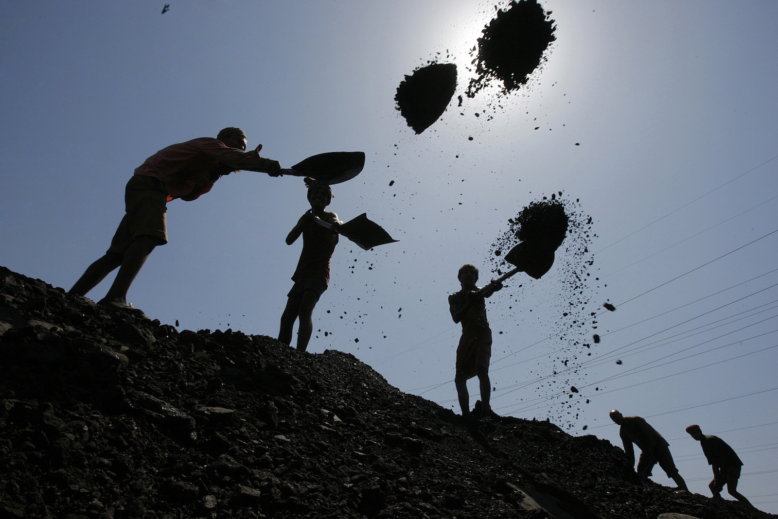 Labourers load coal on trucks at Bari Brahamina in Jammu.