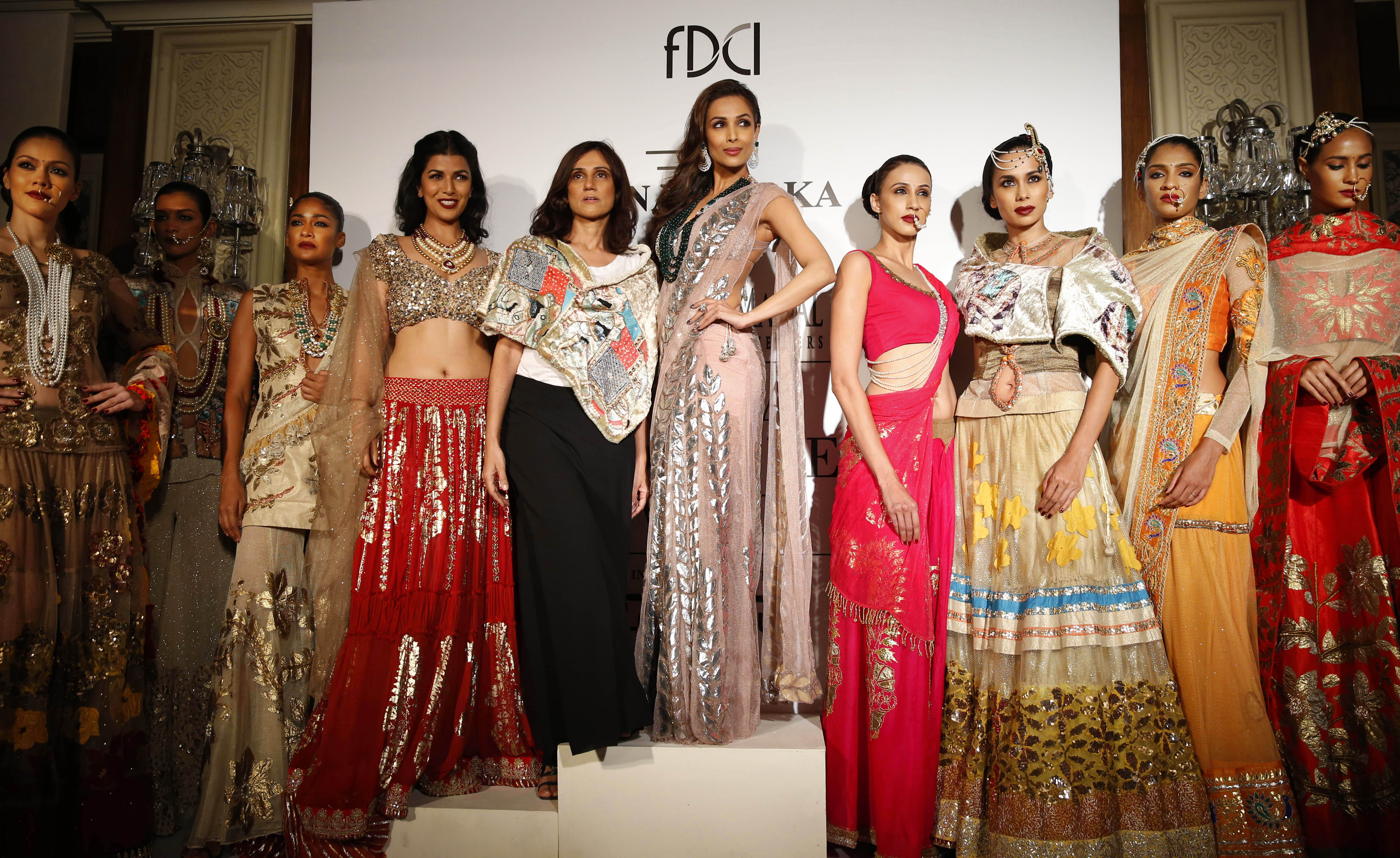 ndian actor Malaika Arora, center right, and designer Rina Dhaka,center left, pose with models displaying dresses created by Dhaka, at the India Couture Week held by Fashion Design Council of India, in New Delhi, India, Wednesday, July 16, 2014. (AP Photo/Saurabh Das)