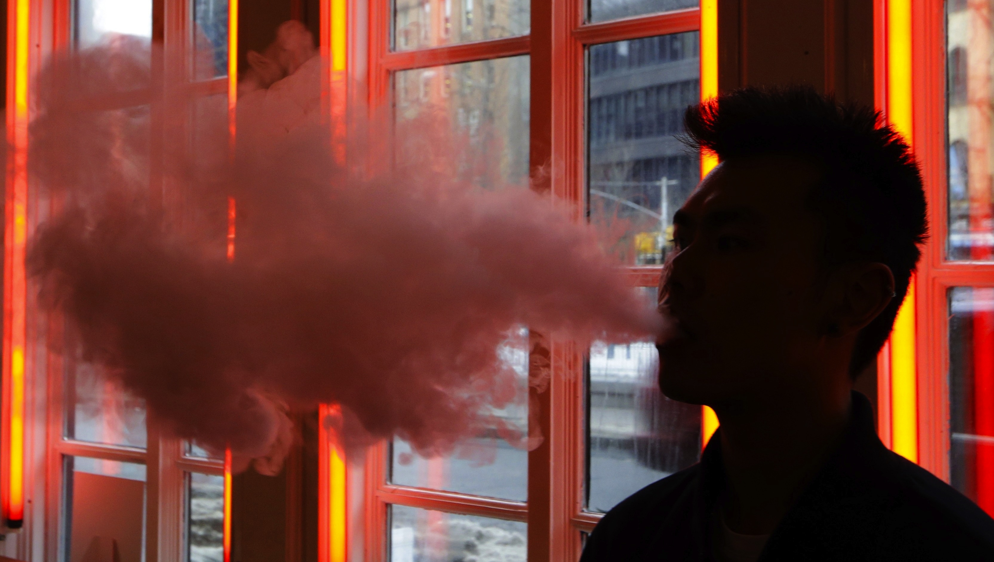 """In this Feb. 20, 2014 photo, a patron exhales vapor from an e-cigarette at the Henley Vaporium in New York. The proprietors are peddling e-cigarettes to """"vapers"""" in a growing movement that now includes celebrity fans and YouTube gurus, online forums and vapefests around the world. (AP Photo/Frank Franklin II)"""