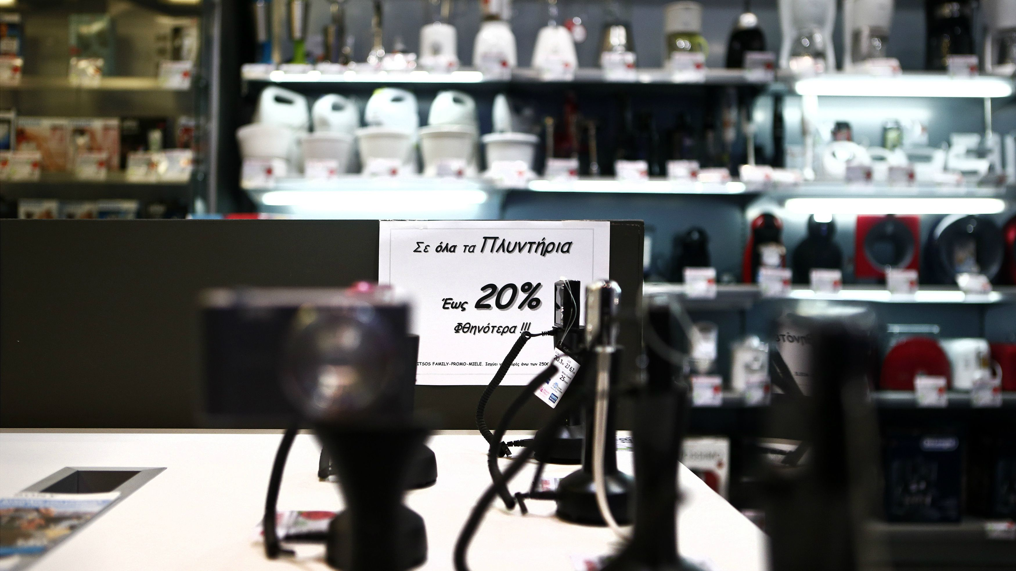 """A sign announcing a discount is pictured at an Electroniki retail chain shop in Athens November 27, 2014. Greece has muddled through 20 consecutive months of deflation, or continuously falling consumer prices ? a phenomenon that economists say could soon infect the whole euro zone. In October, prices fell 1.7 percent from a year earlier. Yet alarm over low inflation in other parts of southern Europe does not echo in Greece. Economists say prices in Greece were unreasonably high for a long time. Between 1995 and 2010, consumer prices rose 17 percent more in Greece than in the euro area overall. Lower prices have since made Greek products more attractive. The sign reads """" 20 percent discount to all washing machines"""". Picture taken November 27, 2014. REUTERS/Alkis Konstantinidis (GREECE - Tags: BUSINESS POLITICS)"""