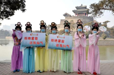 "Members of a local short film club wearing masks and dressed in costumes of Chinese fairies pose for photographs with placards which read ""Say no to smog, return to me fairyism"", during an event to raise awareness of air pollution, at a park in Handan, Hebei province"
