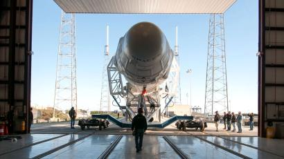 A Falcon 9 rocket leaves a hangar.