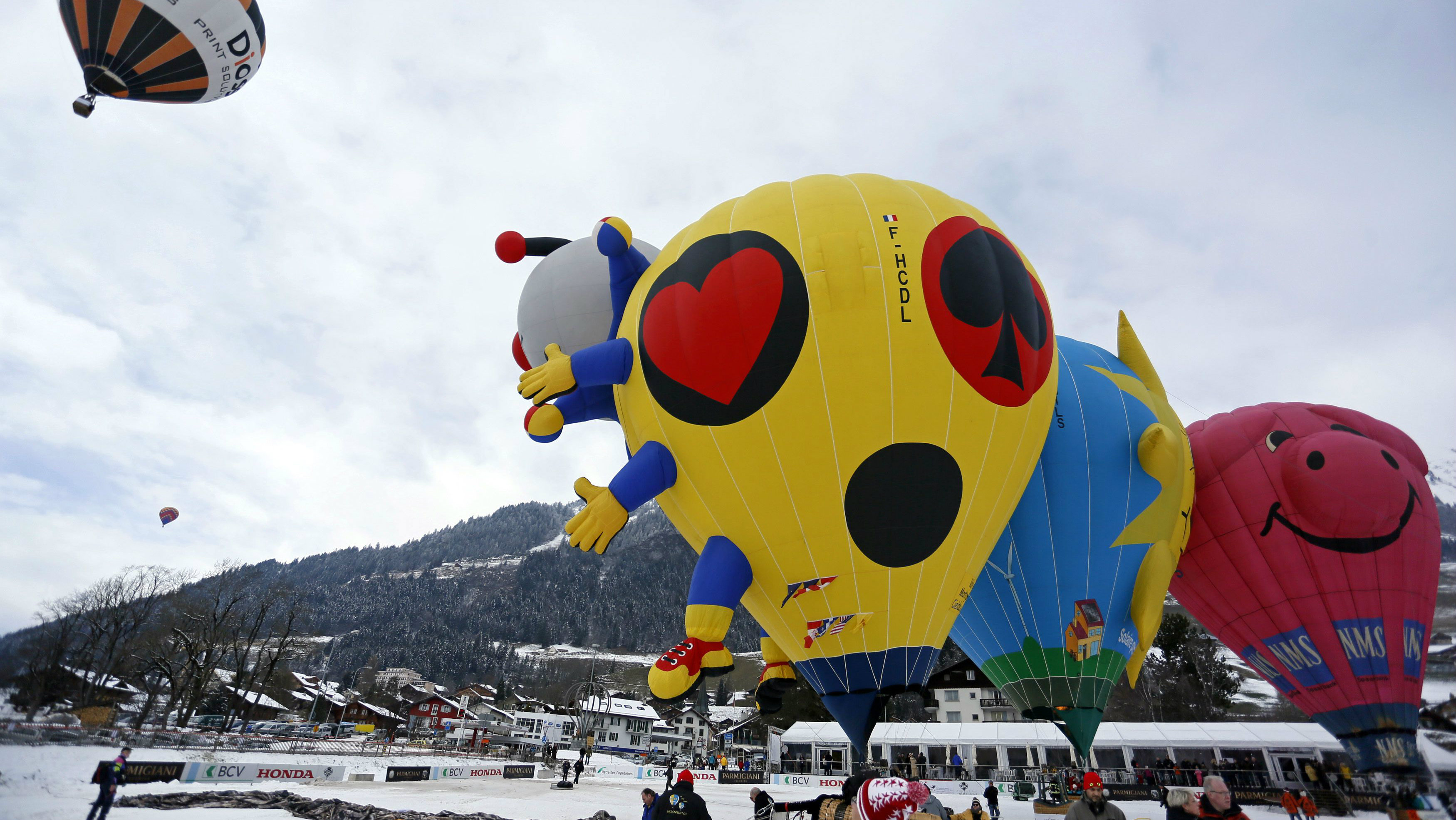 Balloons of all shapes and sizes get ready for take off at the 37th International Hot Air Balloon Week in Chateau-d'Oex, January 24, 2015. According to the organizers, over 80 balloons from 20 countries are participating in the ballooning event in the Swiss mountain resort. REUTERS/Pierre Albouy