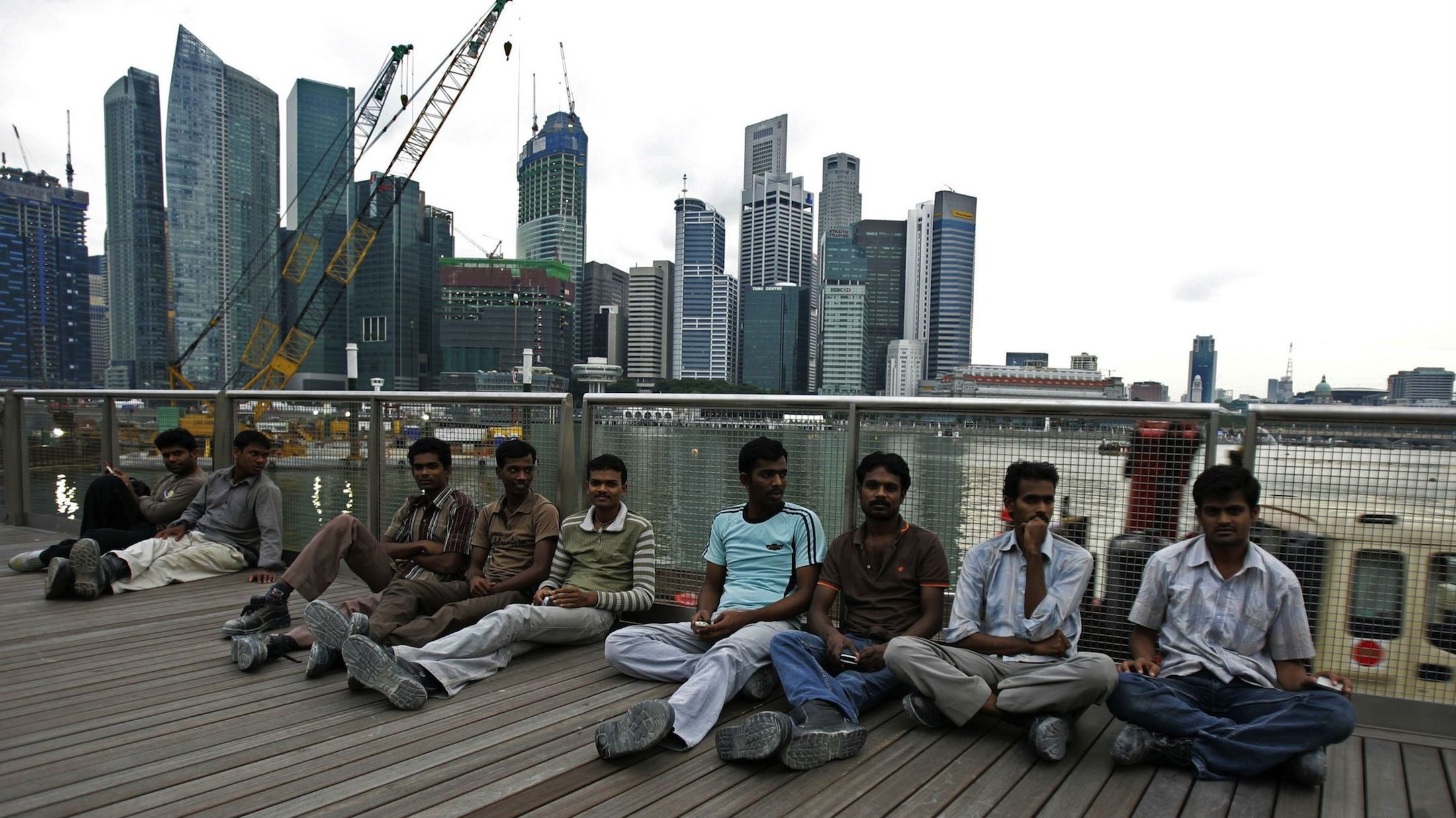 Migrant workers from the Indian sub-continent on their day off sit on an outdoor viewing platform at the recently opened Marina Bay Sands integrated resorts in Singapore August