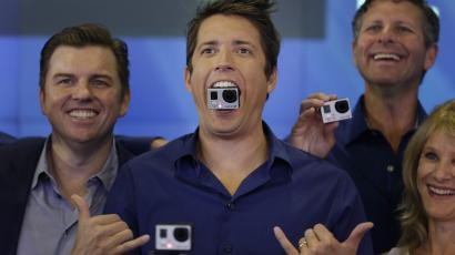 GoPro's CEO Nick Woodman holds a GoPro camera in his mouth as he celebrates his company's IPO at the Nasdaq MarketSite in New York, Thursday, June 26, 2014. GoPro, the maker of wearable sports cameras, loved by mountain climbers, divers, surfers and other extreme sports fans, said late Wednesday it sold 17.8 million shares at $24 each in its initial public offering of stock. (AP Photo/Seth Wenig)