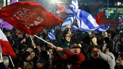 Supporters of radical leftist Syriza party chant slogans and wave Greek national and other flags after winning elections in Athens, January 25, 2015. Greek Prime Minister Antonis Samaras has called Tsipras to congratulate him on winning Sunday's snap election, a spokesman for Syriza and an official of the ruling conservative party said.