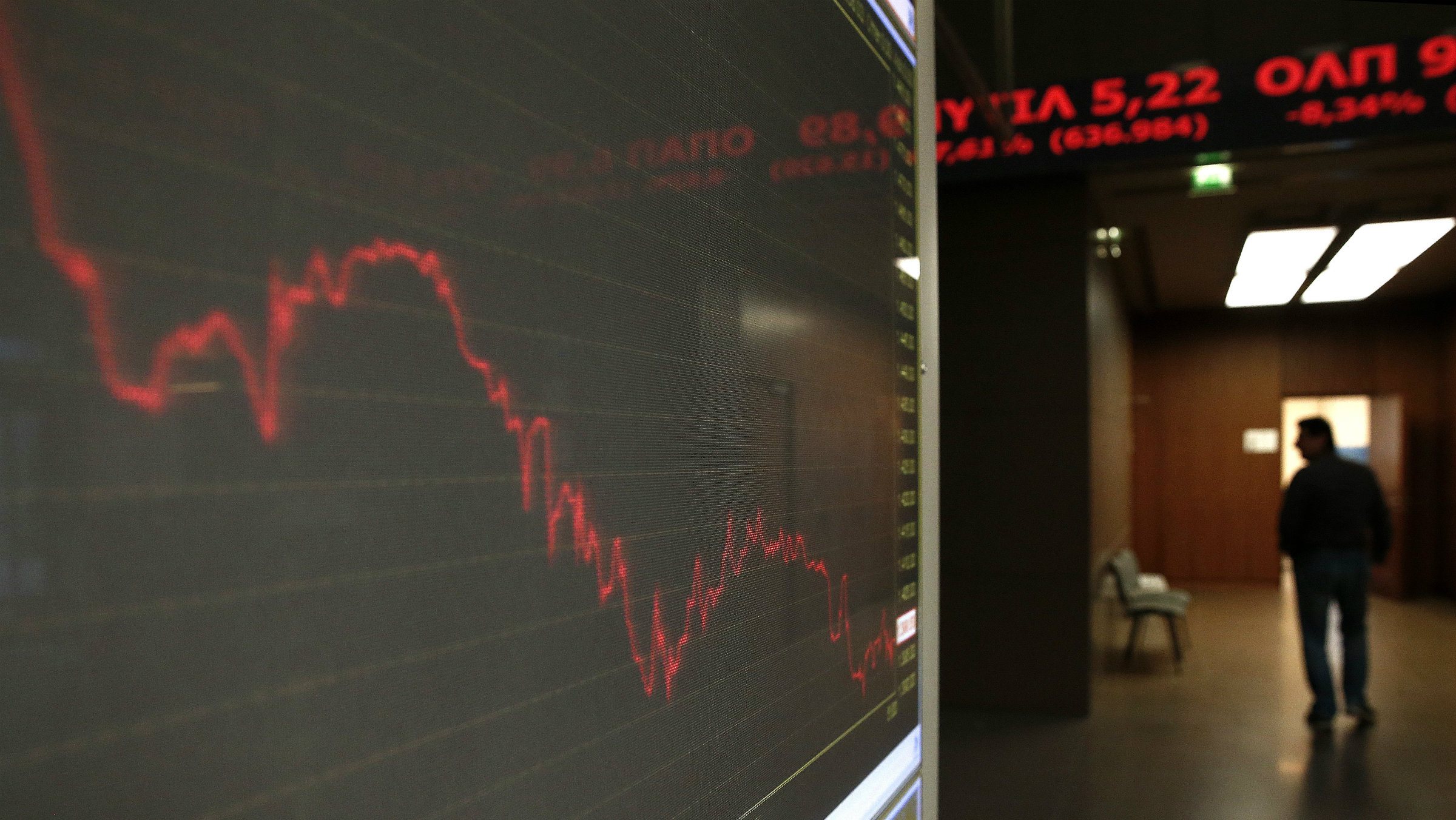 A man walks inside Athens stock exchange as a monitor shows the general index January 28, 2015. The overall Athens stock market fell almost 8 percent, while Greek five-year government bond yields hit around 13.5 percent. This marked their highest level since a 2012 restructuring which wrote off a large proportion of Greek debt held by private investors. REUTERS/Alkis Konstantinidis (GREECE - Tags: POLITICS BUSINESS)