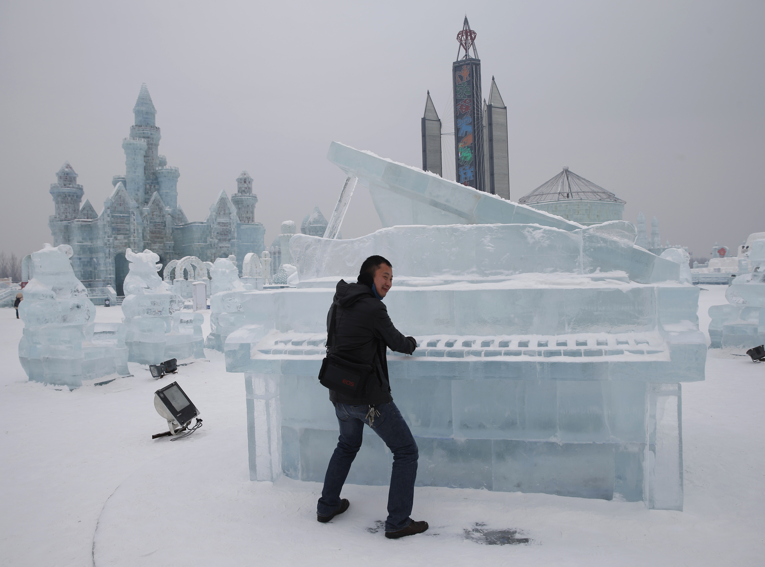 A visitor has his picture taken with a piano-shaped ice sculpture ahead of the 31st Harbin International Ice and Snow Festival in the northern city of Harbin, Heilongjiang province, January 4, 2015. The winter festival will be officially opened on January 5, 2015. REUTERS/Kim Kyung-Hoon
