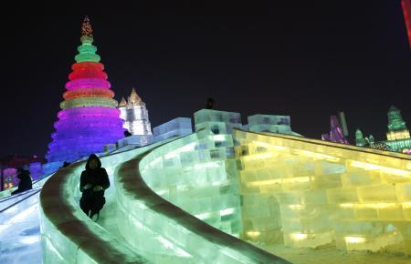 A man rides a slide on an ice sculpture illuminated by coloured lights during a trial operation ahead of the 31st Harbin International Ice and Snow Festival in the northern city of Harbin, Heilongjiang province, January 4, 2015. The winter festival will be officially opened on January 5, 2015. REUTERS/Kim Kyung-Hoon