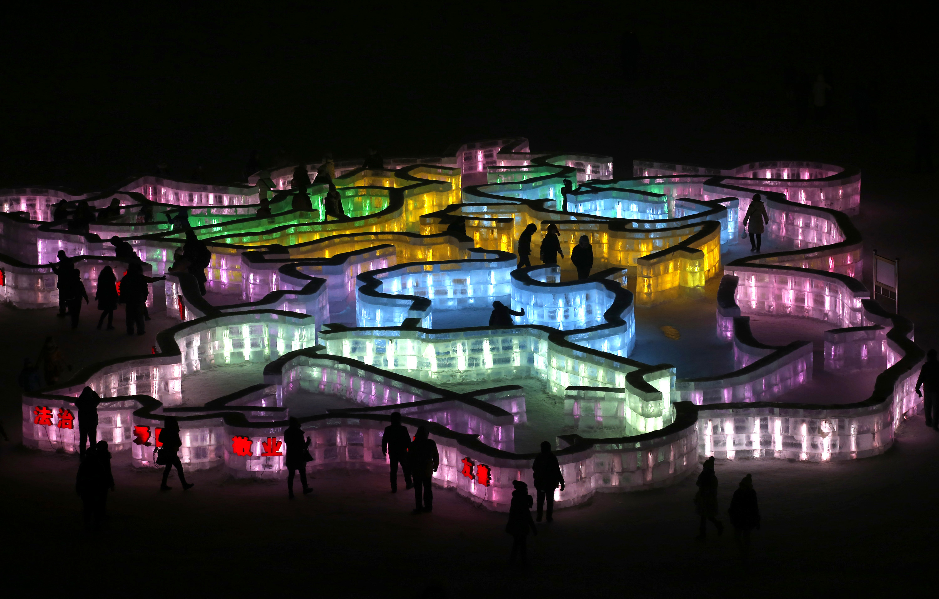 People visit a maze which was built by ice bricks and illuminated by coloured lights during a trial operation ahead of the 31st Harbin International Ice and Snow Festival in the northern city of Harbin, Heilongjiang province, January 4, 2015. The winter festival will be officially opened on January 5, 2015. REUTERS/Kim Kyung-Hoon