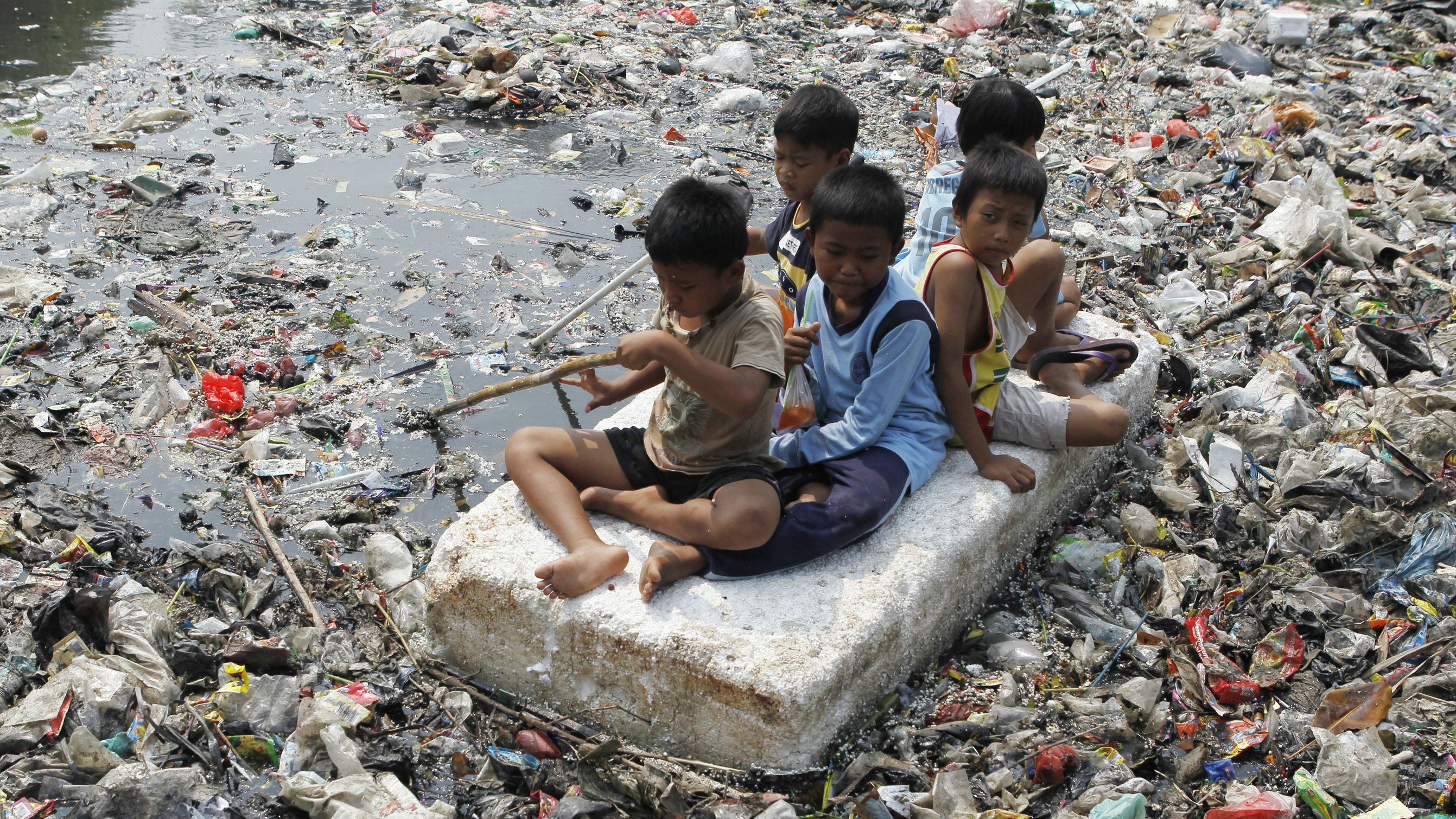 Children sitting on a makeshift raft play in a river full of rubbish in a slum area of Jakarta September 19, 2012. REUTERS/Enny Nurahen