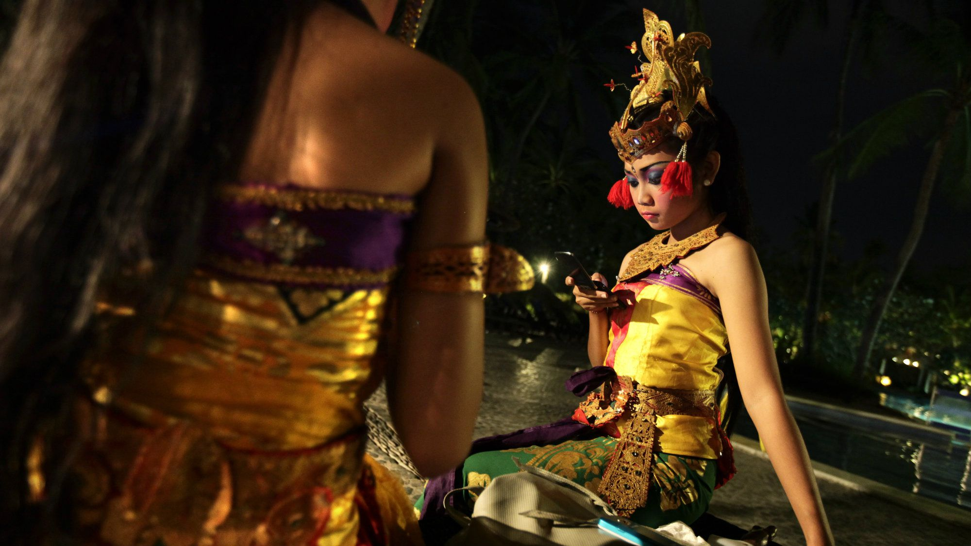 Indonesian traditional dancers using mobile phones