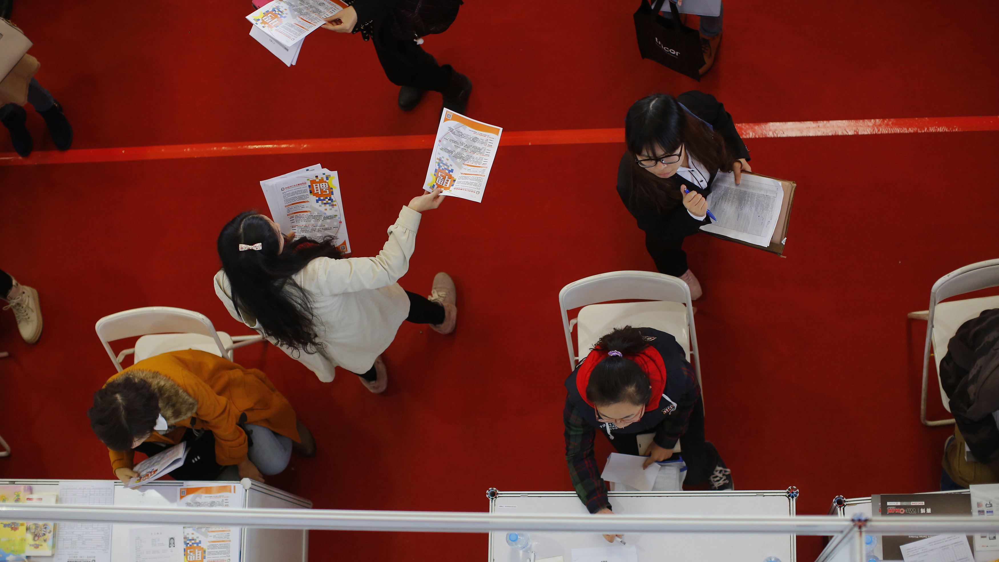 Students visit booths during a job fair at Donghua University in Shanghai November 20, 2014. China's economy faces increasing downward pressure in 2015 while the country pushes forward reforms to keep economic growth stable, the top economic planning body said on Wednesday.