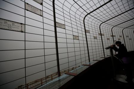 A visitor is silhouetted at an observatory tower during a polluted day in Beijing January 15, 2015. Beijing issued its first smog alert of 2015 on Tuesday. Stagnant and humid air has aggravated the city's air pollution, causing the smog to linger, according to Xinhua News Agency. REUTERS/Kim Kyung-Hoon (CHINA - Tags: ENVIRONMENT)