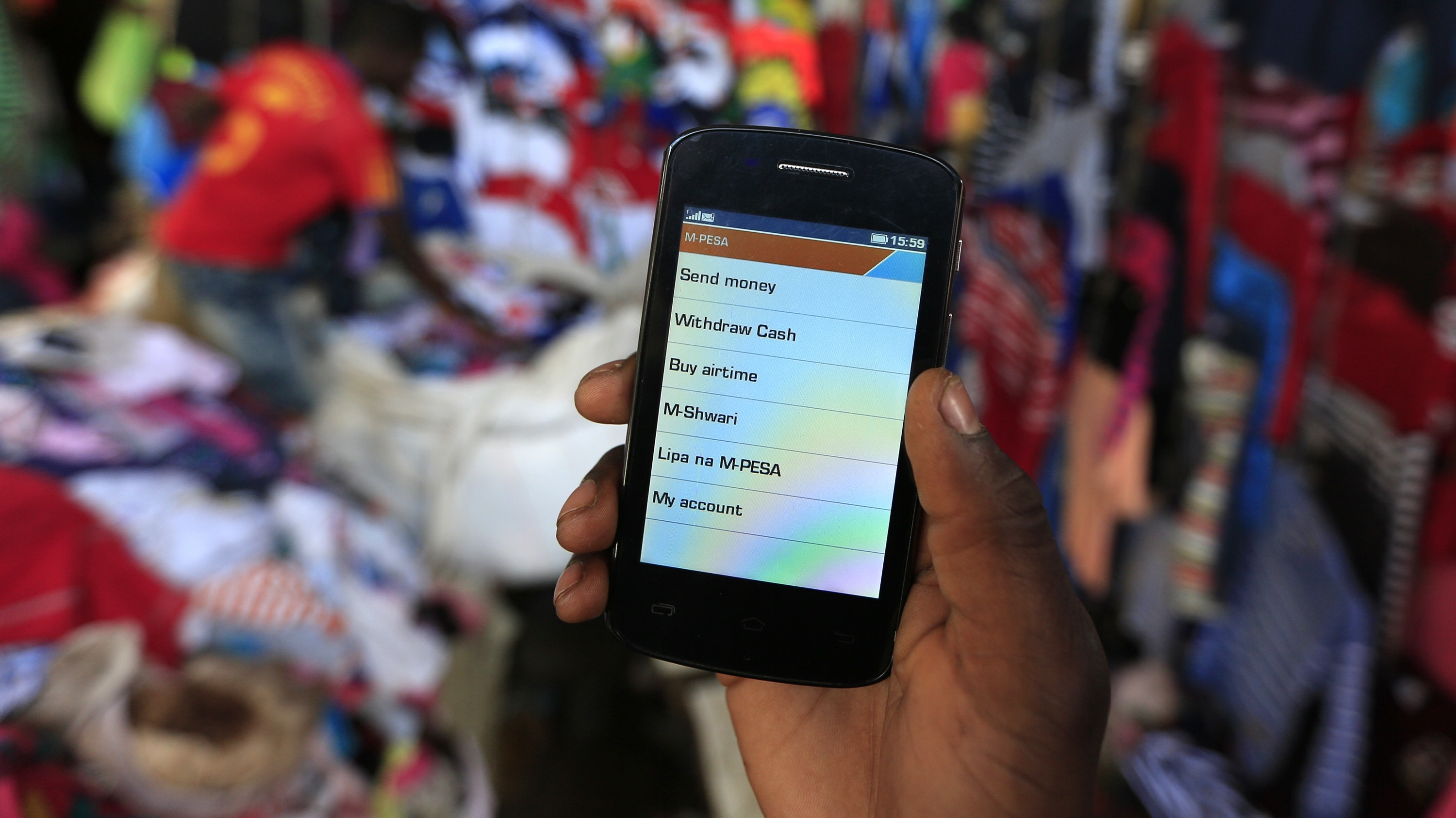 A man holds up his mobile phone showing a M-Pesa mobile money transaction page for the photographer at an open air market in Kibera in Kenya's capital Nairobi December 31, 2014. Safaricom, Kenya's biggest telecoms firm, is a model of how technology can be used to financially include millions of people with mobile telephones but without access to traditional infrastructure such as the banks that are available to the wealthy or those living in cities. Safaricom in 2007 pioneered its M-Pesa mobile money transfer technology, now used across Africa, Asia and Europe. It proved that money can be made from people who earn a few dollars a day. REUTERS/Noor Khamis
