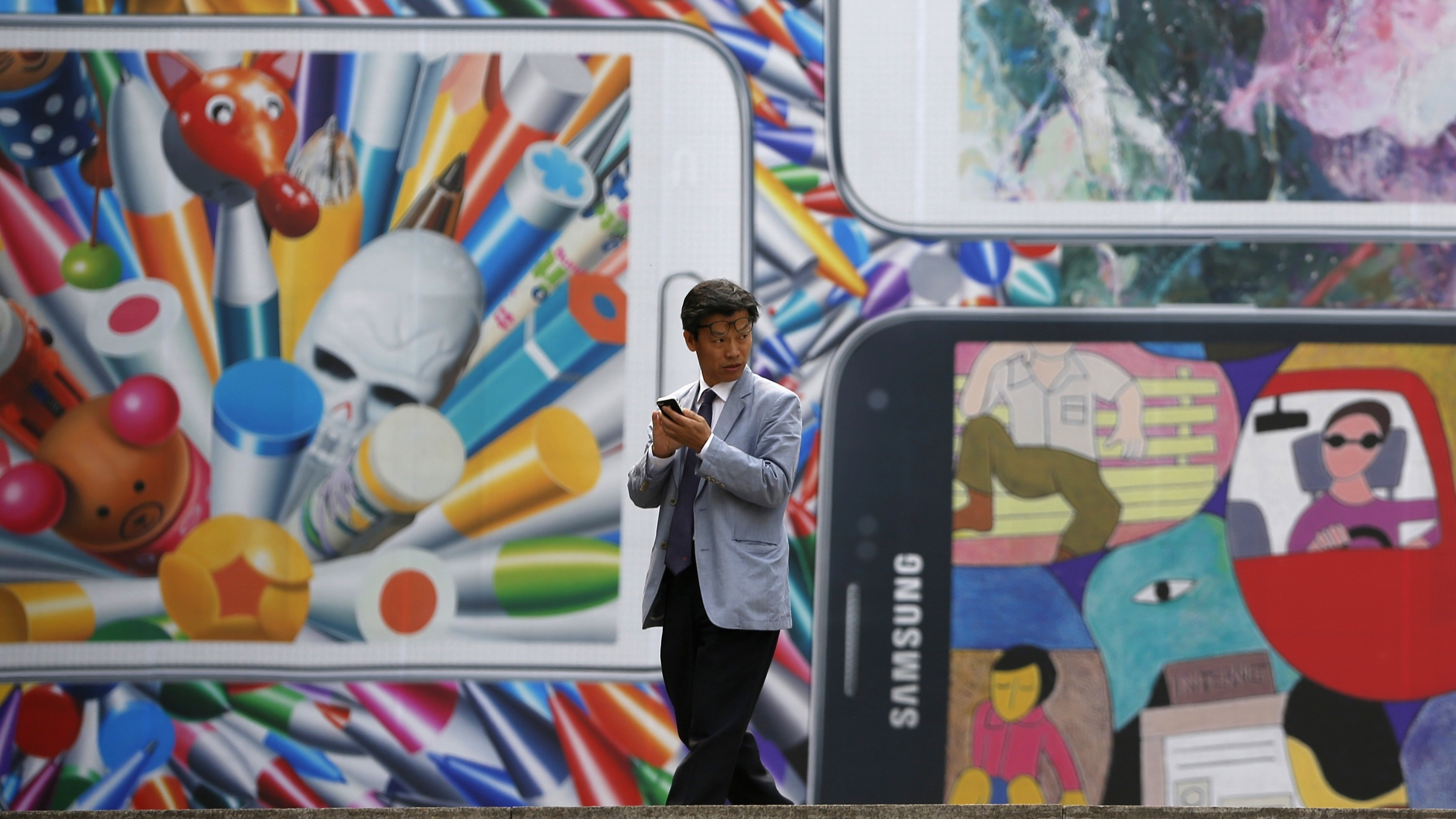 A man uses his mobile phone in front of a giant advertisement promoting Samsung Electronics' new Galaxy S5 smartphone, at an art hall in central Seoul April 15, 2014. Samsung Electronics Co Ltd's new Galaxy S5 smartphone should outsell its predecessor and defy predictions that the South Korean titan's latest model will struggle in a tough market for high-end handsets, Yoon Han-kil, senior vice president of Samsung's product strategy team, told Reuters in an interview. Picture taken on April 15, 2014. To match Interview SAMSUNG-ELEC-SALES/ REUTERS/Kim Hong-Ji