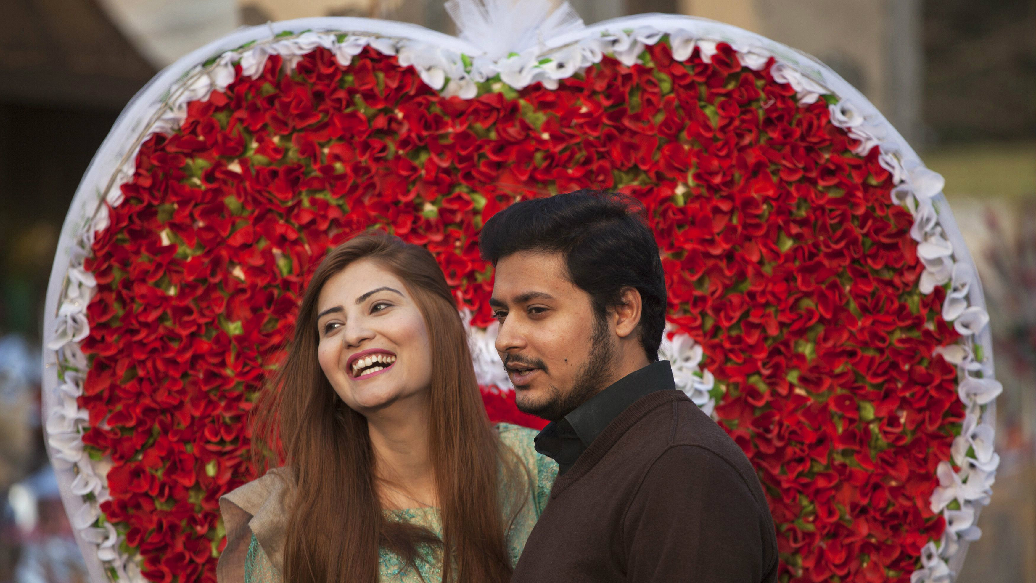 A couple smiles as they stand next to a heart shape paper-flower decoration at flower market on the Valentine's Day in Islamabad February 14, 2014. REUTERS/Mian Khursheed