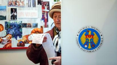 A woman reads her ballot during a parliamentary election at a polling station in Chisinau November 30, 2014. Ex-Soviet Moldova voted on Sunday in an election whose outcome might slow, though not halt, its moves to join the European mainstream in defiance of Russia, which has banned its wines and other prime exports, hitting its economy hard.