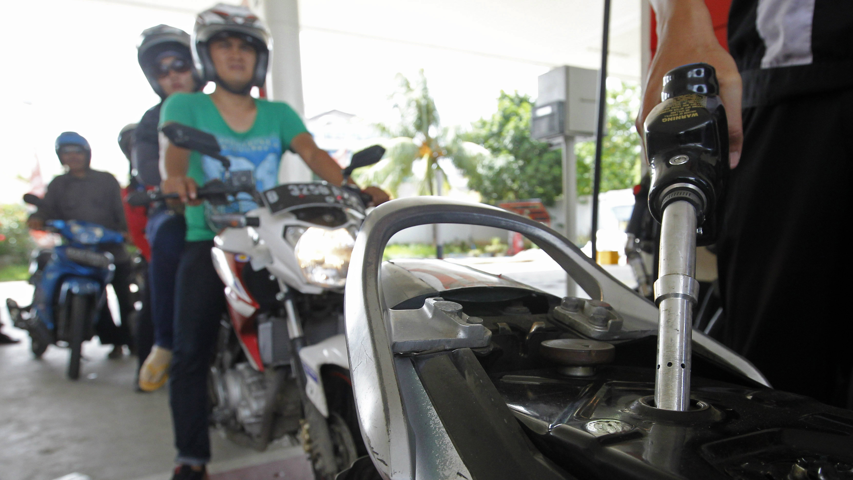 An employee of state-owned Pertamina refuels a motorcycle at its petrol station in Jakarta, December 17, 2014.