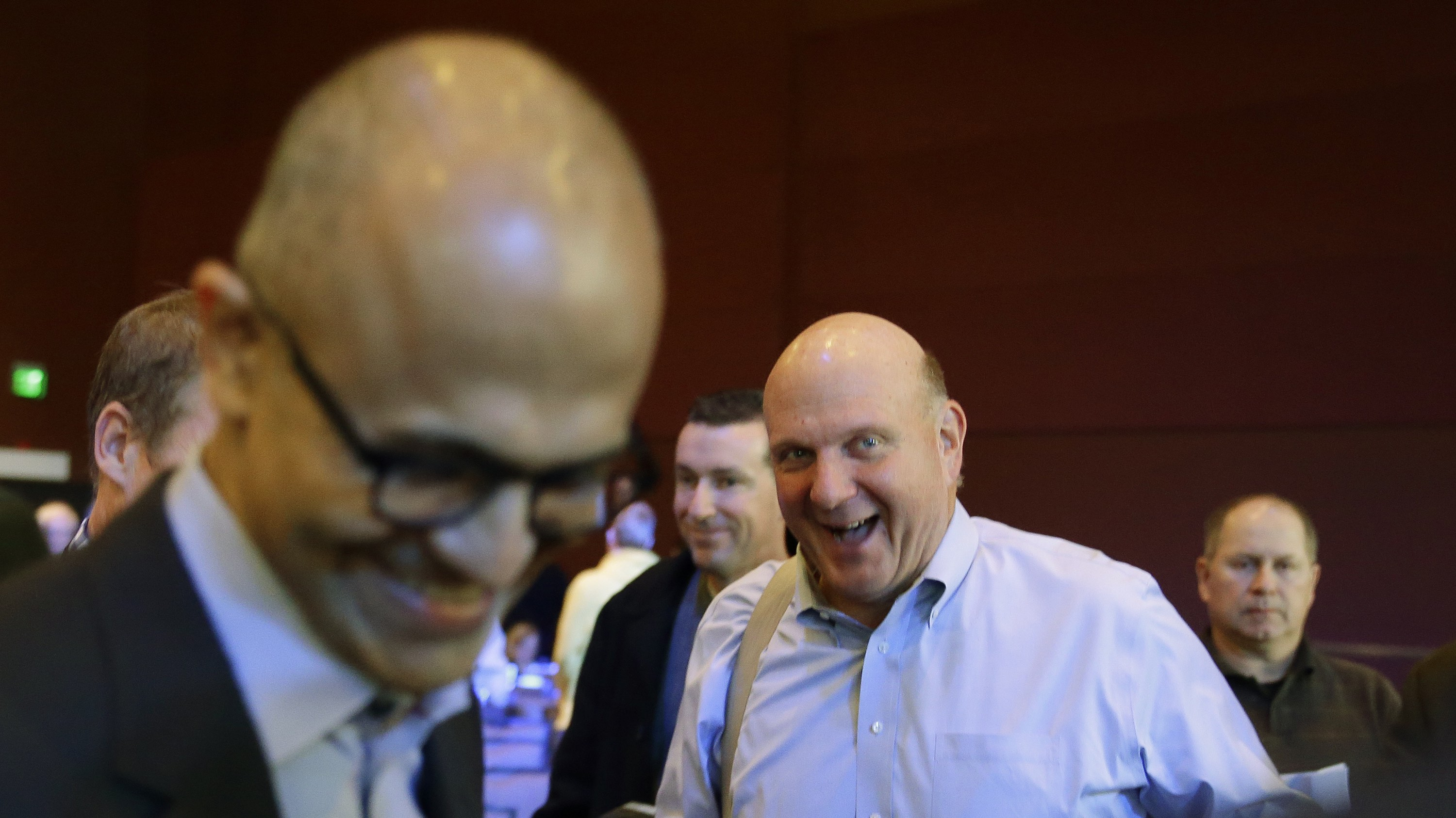 Former Microsoft CEO Steve Ballmer, right, laughs after shaking hands with current CEO Satya Nadella, left, Wednesday, Dec. 3, 2014, at Microsoft Corp.'s annual shareholders meeting, in Bellevue, Wash. (AP Photo/Ted S. Warren)