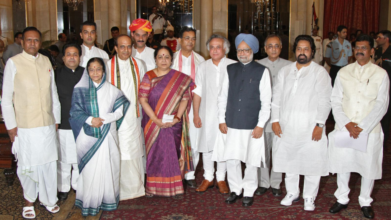 L-R) Newly appointed India's Steel Minister Beni Prasad Verma, Minister of State for Parliamentary Affairs Rajiv Shukla, Minister of State for Communications and Information Technology Milind Deora, President Pratibha Patil, Railways Minister Dinesh Trivedi, Minister of State for Home Affairs Jitendra Singh, Minister of State for Environment and Forests Jayanthi Natarajan, Minister of State for the Development of North Eastern Region Paban Singh Ghatowar, Rural Development Minister Jairam Ramesh, Prime Minister Manmohan Singh, Tribal Affairs and Panchayati Raj Minister Kishore Chandra Deo, Minister of State for Health and Family Welfare Sudip Bandopadhyaya and Minister of State for Agriculture and Food Processing Industries Charan Das Mahant pose for pictures after the swearing-in ceremony of the reshuffled cabinet at the presidential palace in New Delhi July 12, 2011. Prime Minister Manmohan Singh retained key allies in a cabinet reshuffle on Tuesday, shunning big changes in a bid to hold onto power amid charges of graft and policy paralysis.