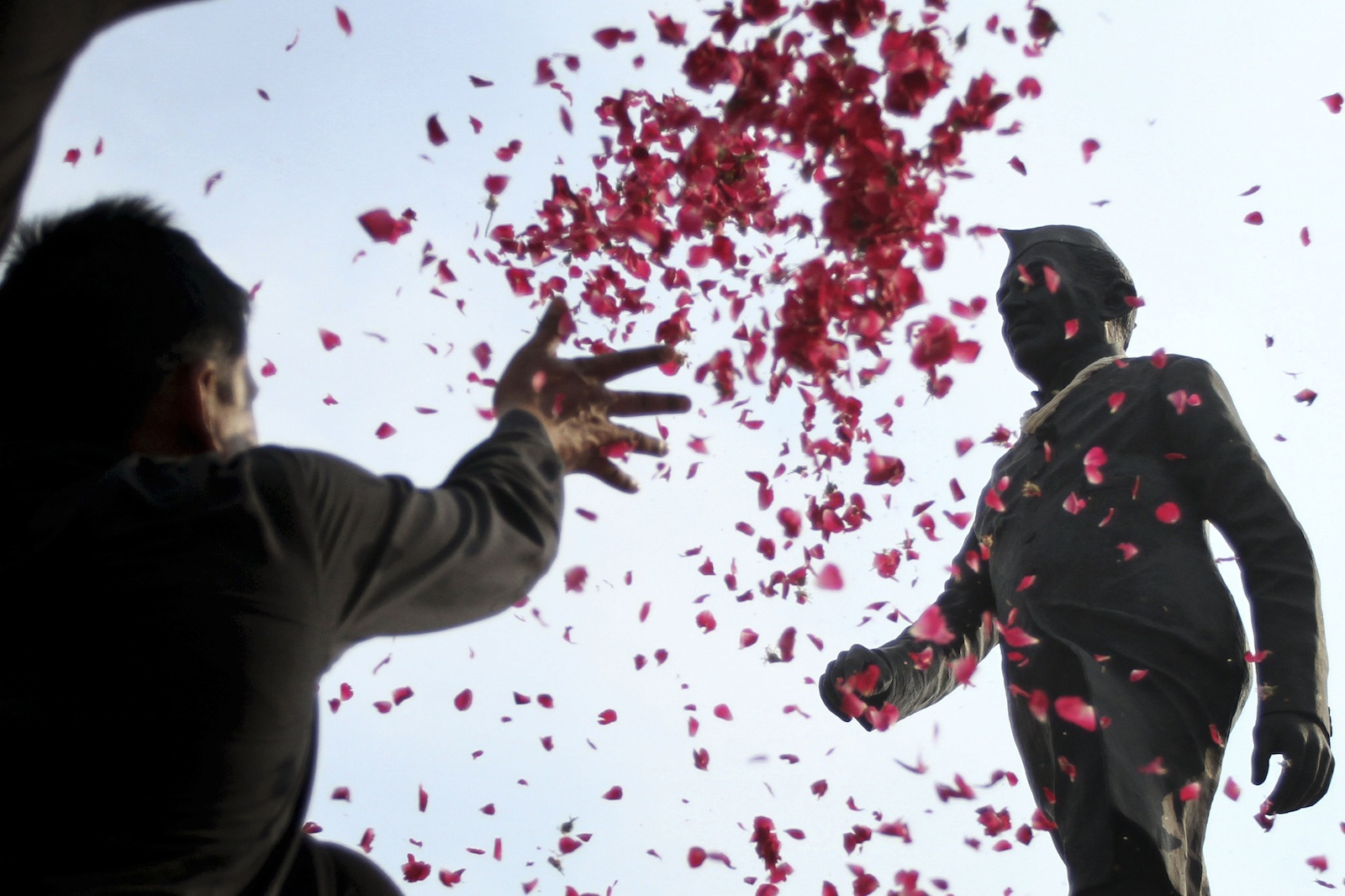 An Indian man throws petals on a statue of India's first prime minister Jawaharlal Nehru on his birth anniversary in Ahmadabad, India, Friday, Nov. 14, 2014.