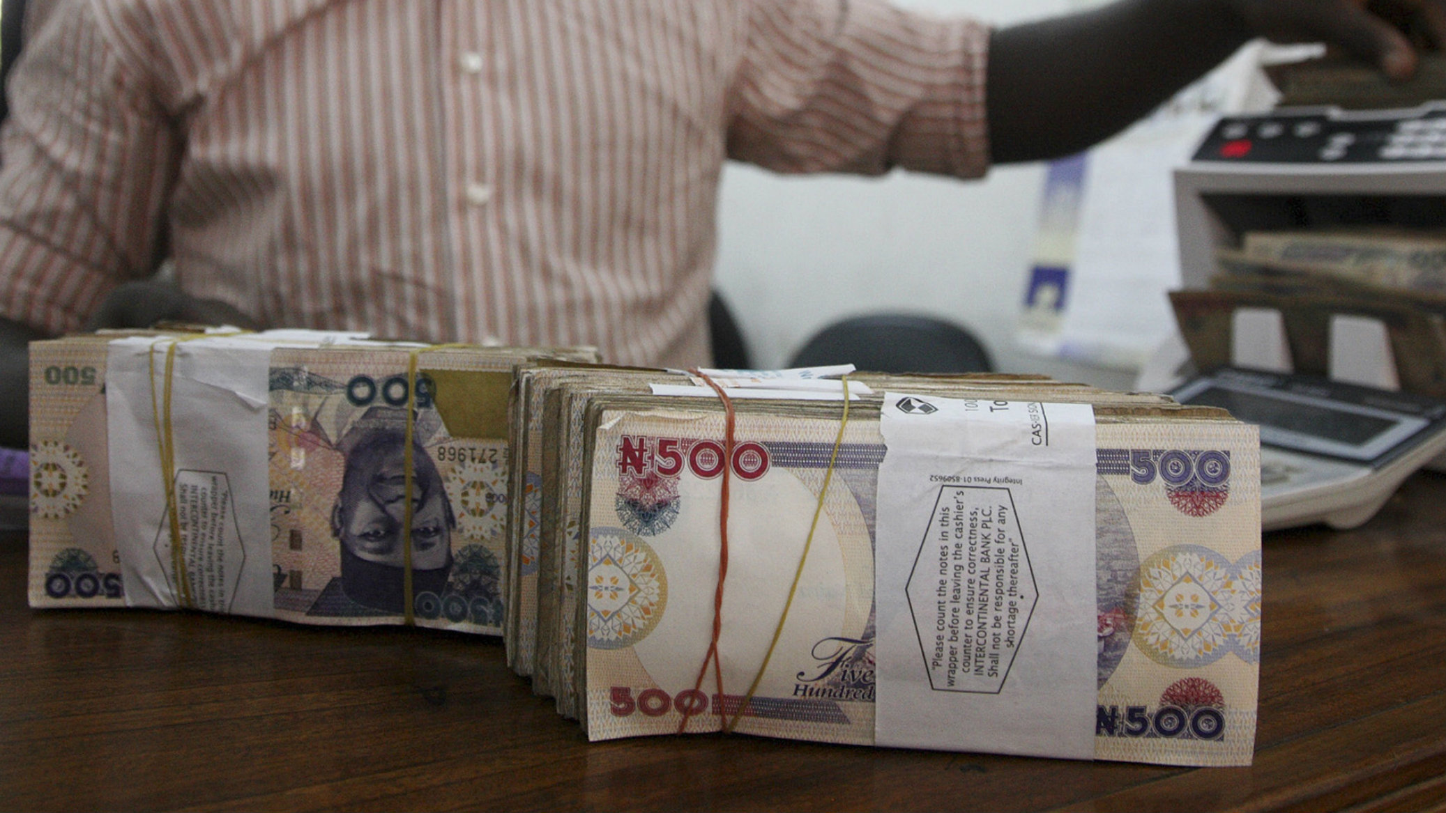 A money dealer counts the Nigerian naira on a machine in his office in the commercial capital of Lagos, January 13, 2009. Nigeria's central bank governor moved to reassure investors on Tuesday following sharp falls in the local naira currency, saying the depreciation had protected its foreign reserves and the exchange rate would soon stabilise. REUTERS/Akintunde Akinleye (NIGERIA)
