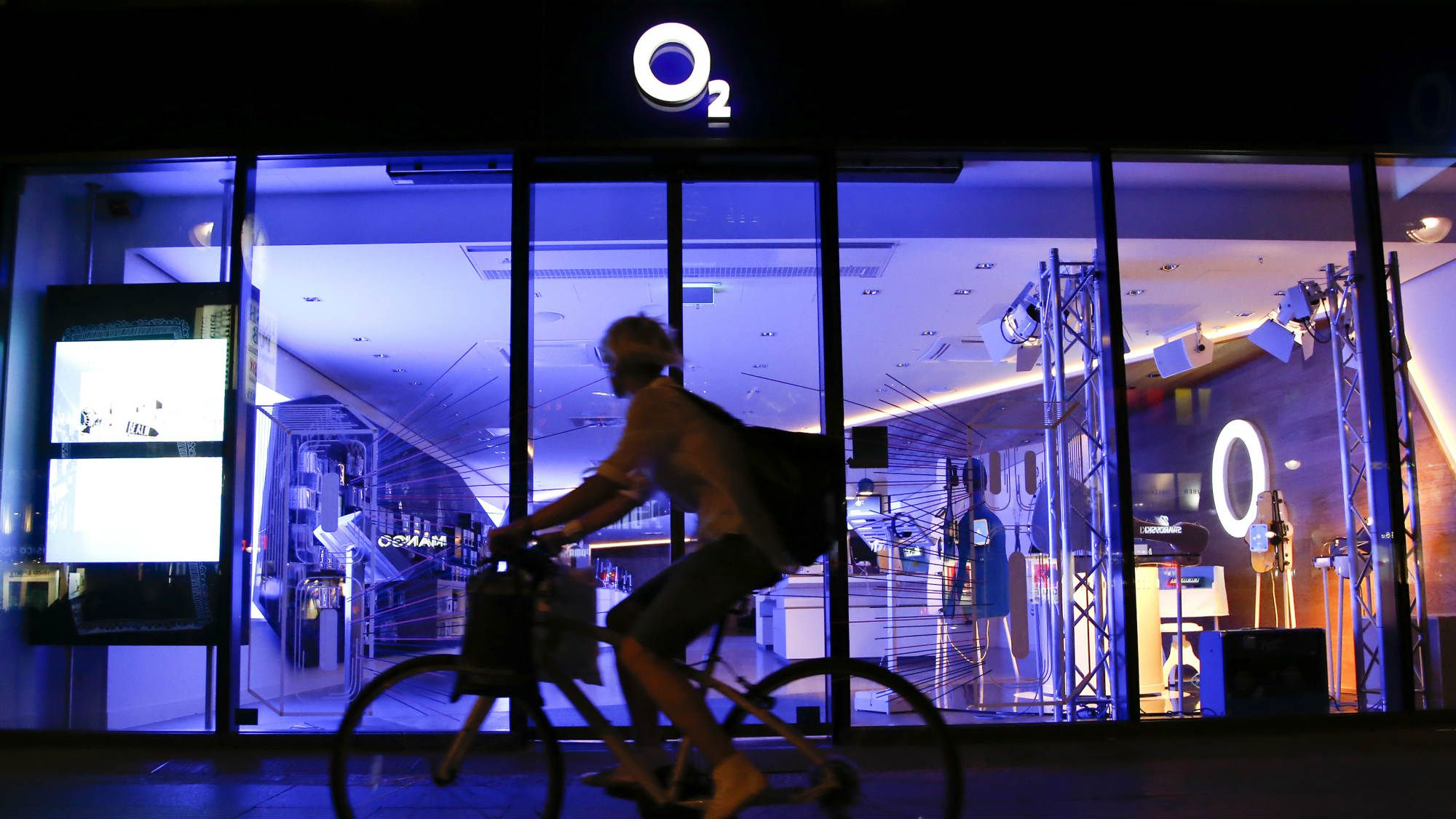 A cyclist passes the front of a O2 Deutschland shop in Berlin July 23, 2013. E-Plus, the German mobile phone operator, expects regulators may demand remedies in order to approve its sale to Telefonica Deutschland for some 8.1 billion euros ($10.7 billion), its CEO told Reuters.REUTERS/Fabrizio Bensch (GERMANY - Tags: BUSINESS TELECOMS)