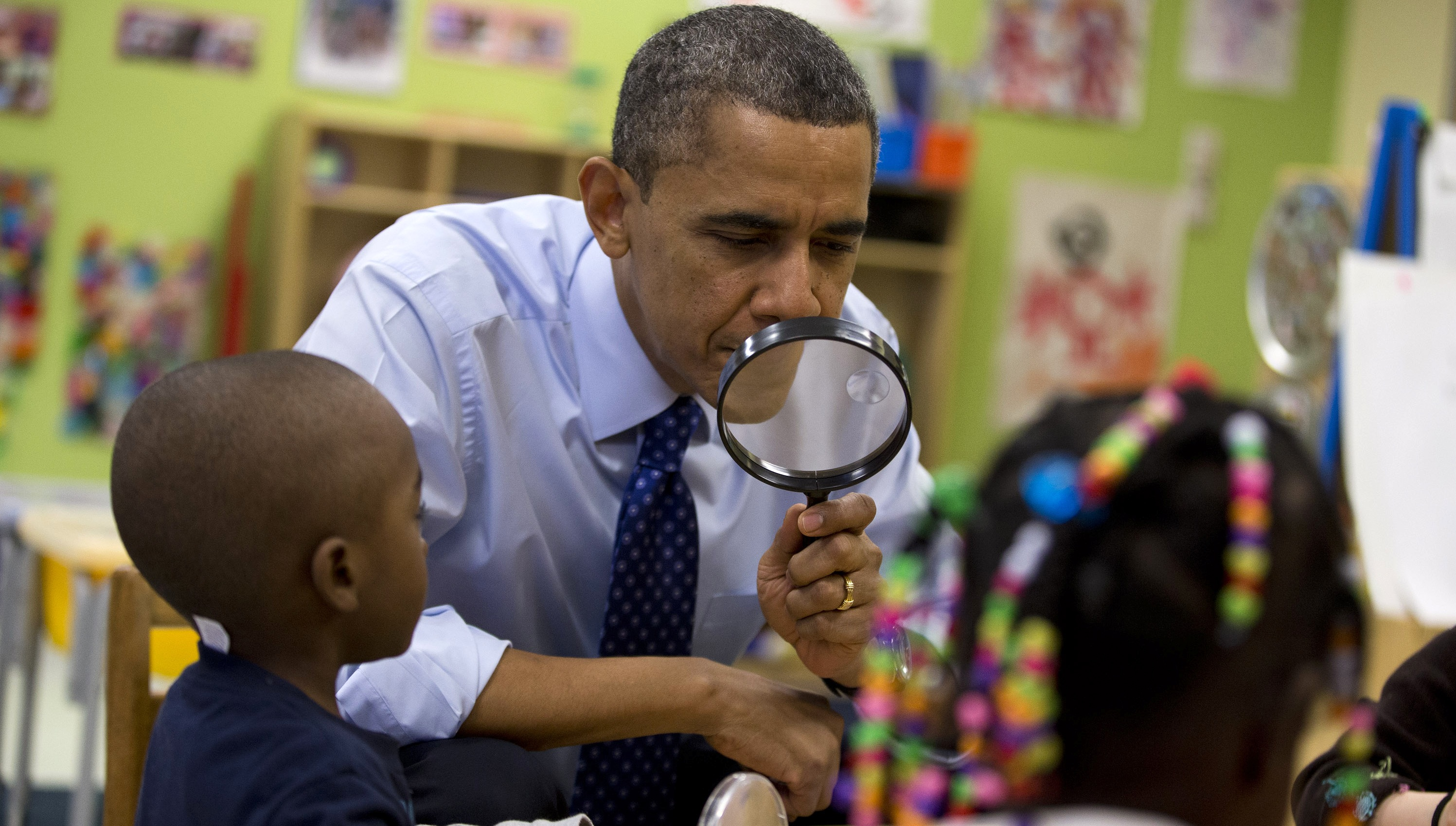 President Barack Obama looks through a magnifying glass during a learning game at a pre-kindergarten classroom at College Heights Early Childhood Learning Center in Decatur, Ga., Thursday, Feb. 14, 2013. The president is traveling to promote his economic and educational plan that he highlighted in his State of the Union address. (AP Photo/ Evan Vucci)