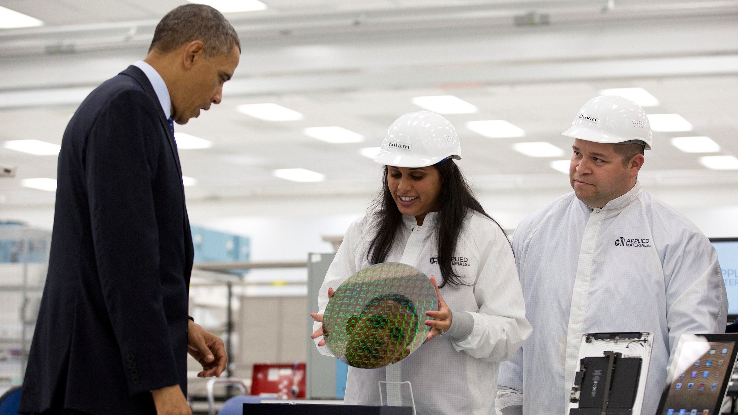 U.S. President Barack Obama is reflected in a silicon wafer during a tour of Applied Materials in Austin, Texas, May 9, 2013.