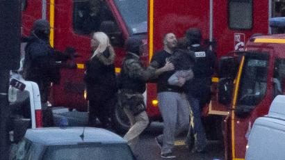 A security officer directs released hostages after they stormed a kosher market to end a hostage situation, Paris, Friday, Jan. 9, 2015. Explosions and gunshots were heard as police forces stormed a kosher grocery in Paris where a gunman was holding at least five people hostage. (AP Photo/Michel Euler)