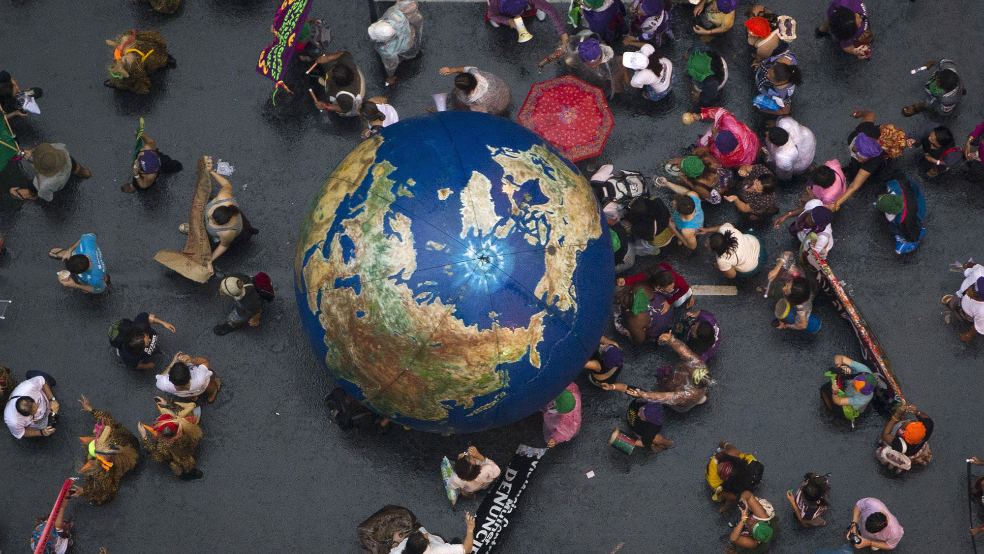 """Activists push an inflatable globe during a """"Global March"""" as part of the People's Summit for Social and Environmental Justice in Defense of the Commons, a parallel event during the UN Conference on Sustainable Development, or Rio+20, in Rio de Janeiro, Brazil, Wednesday, June 20, 2012."""