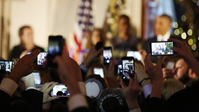 people using phones at obama event