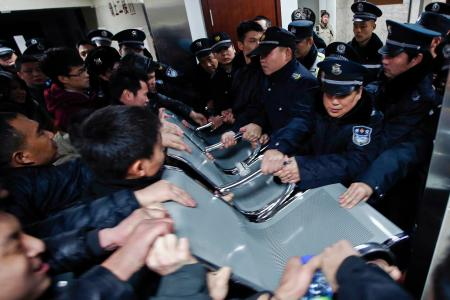 People clash with police as they try to visit relatives injured in a stampede, at a hospital in central Shanghai on New Year's Day.