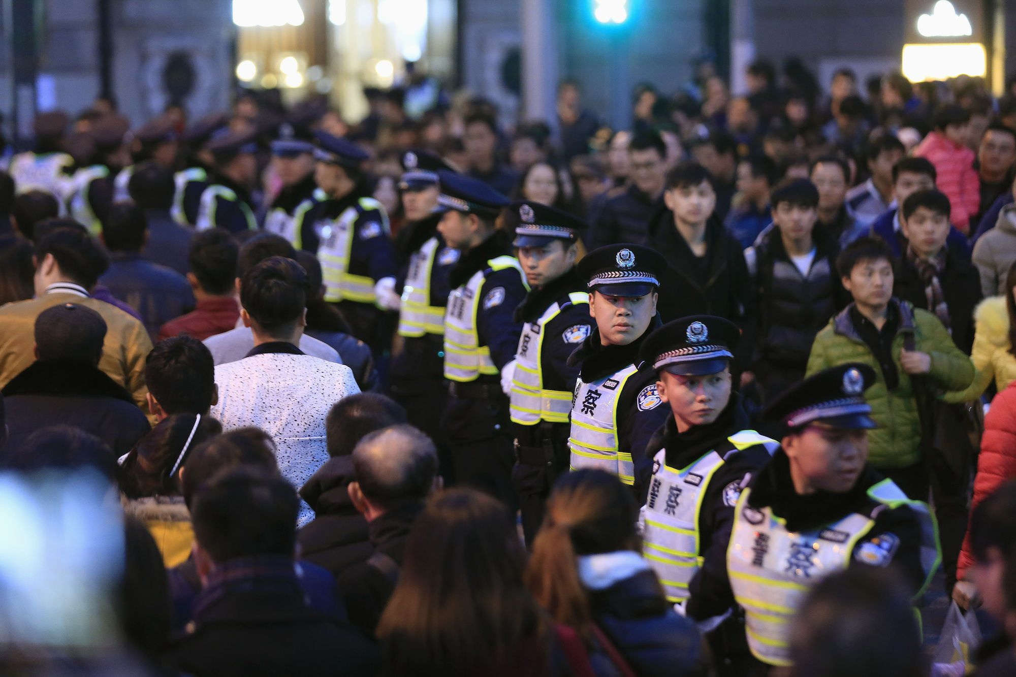 Policemen stand guard on the location where people were killed in a stampede incident during a New Year's celebration