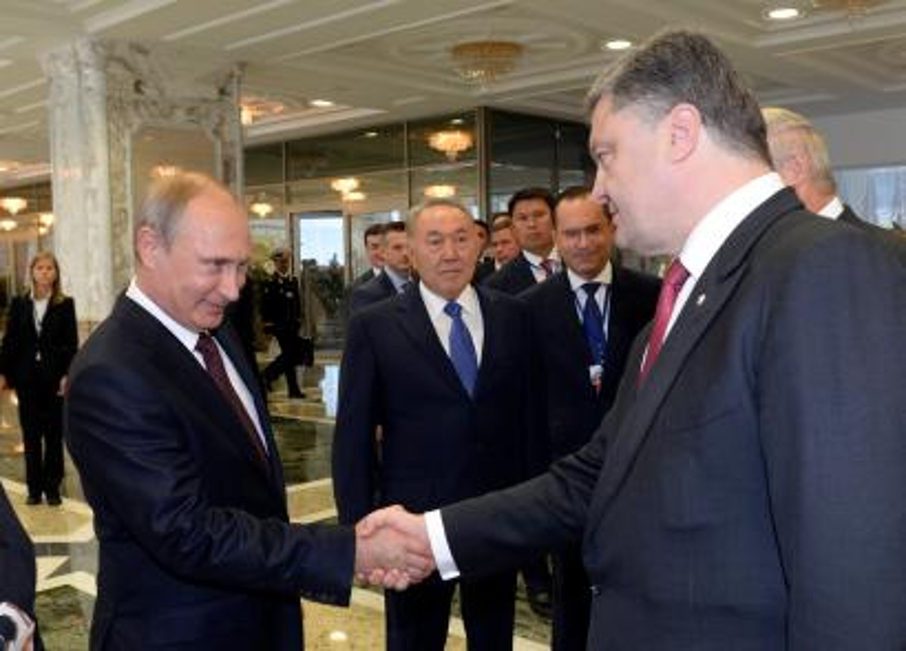 Russian President Vladimir Putin (L) shakes hands with his Ukrainian counterpart Petro Poroshenko, as Kazakh President Nursultan Nazarbayev (C) stands nearby, in Minsk August 26, 2014.
