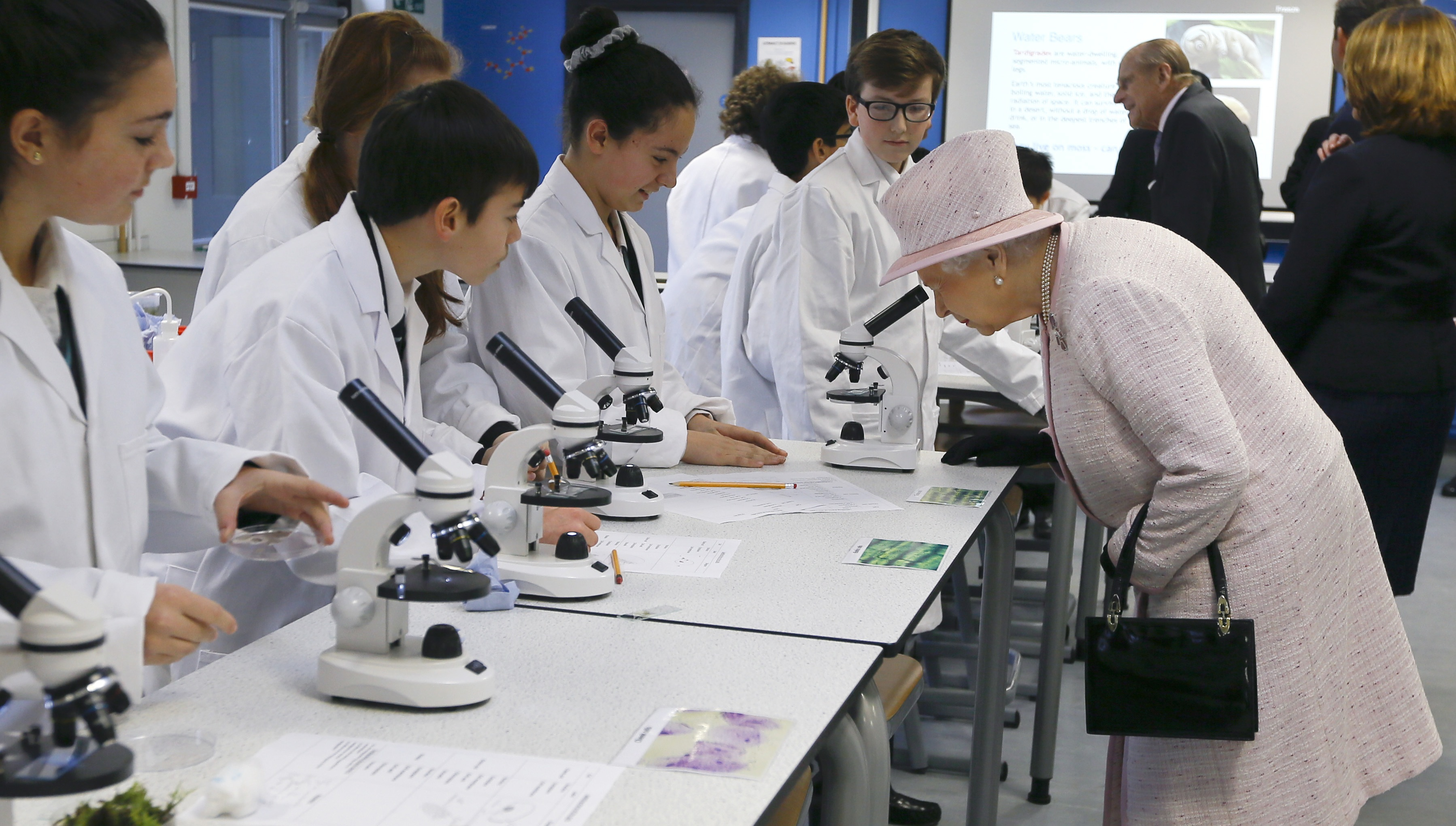 Britain's Queen Elizabeth II looks through a microscope as she tours a science lesson, during a visit to Holyport College near Maidenhead, Berkshire in England, Friday, Nov. 28, 2014. Holyport College is an all-ability, co-educational day and boarding school for students aged 11 to 19 years and is a state-funded 'free school,' which opened in Sept. 2014. (AP Photo/Kirsty Wigglesworth, Pool)