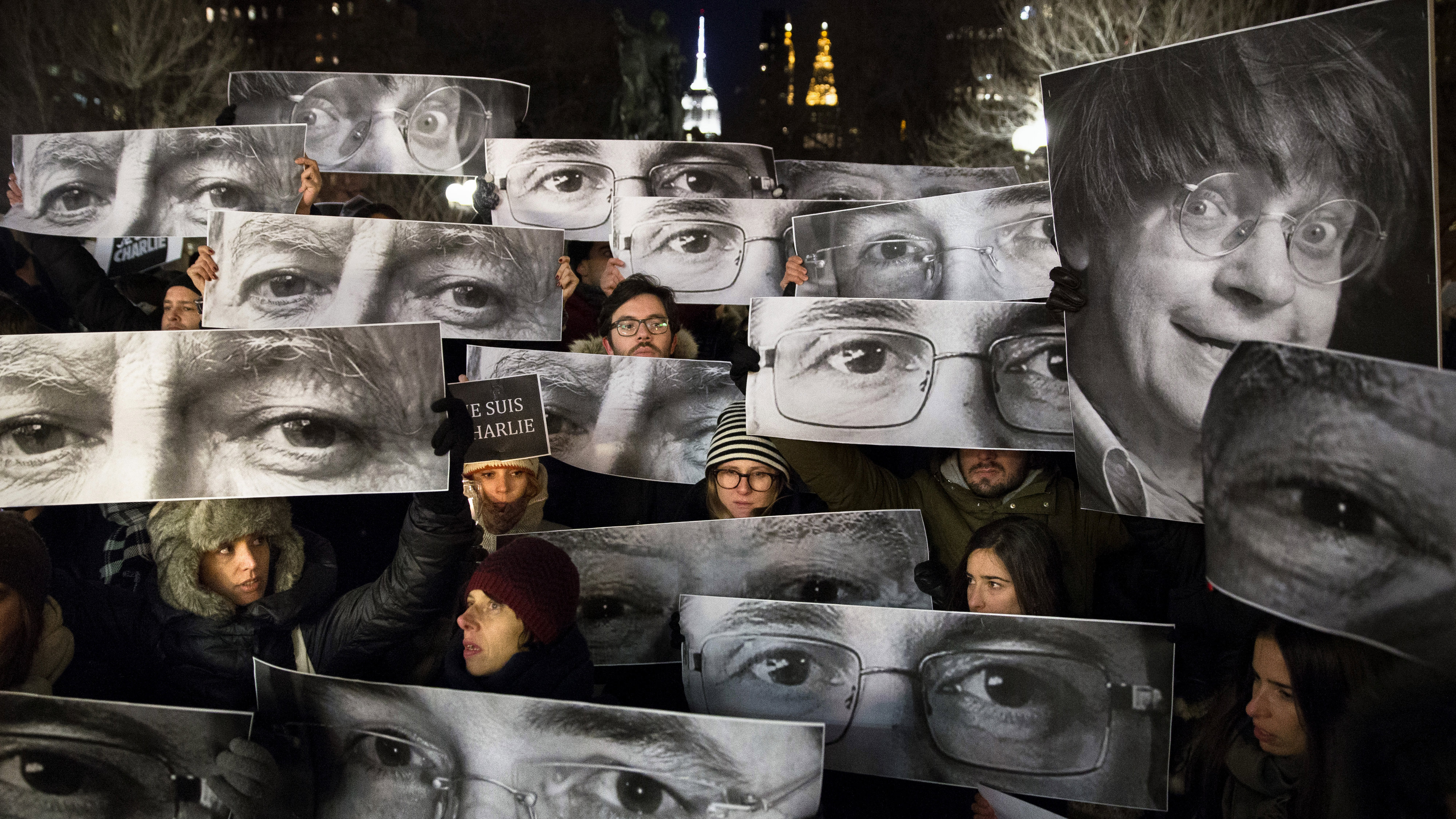 AP10ThingsToSee - Mourners hold signs depicting victim's eyes during a rally in support of Charlie Hebdo, a French satirical weekly newspaper that fell victim to an terrorist attack, Wednesday, Jan. 7, 2015, at Union Square in New York. French officials said 12 people were killed when masked gunmen stormed the Paris offices of the periodical that had caricatured the Prophet Muhammad.