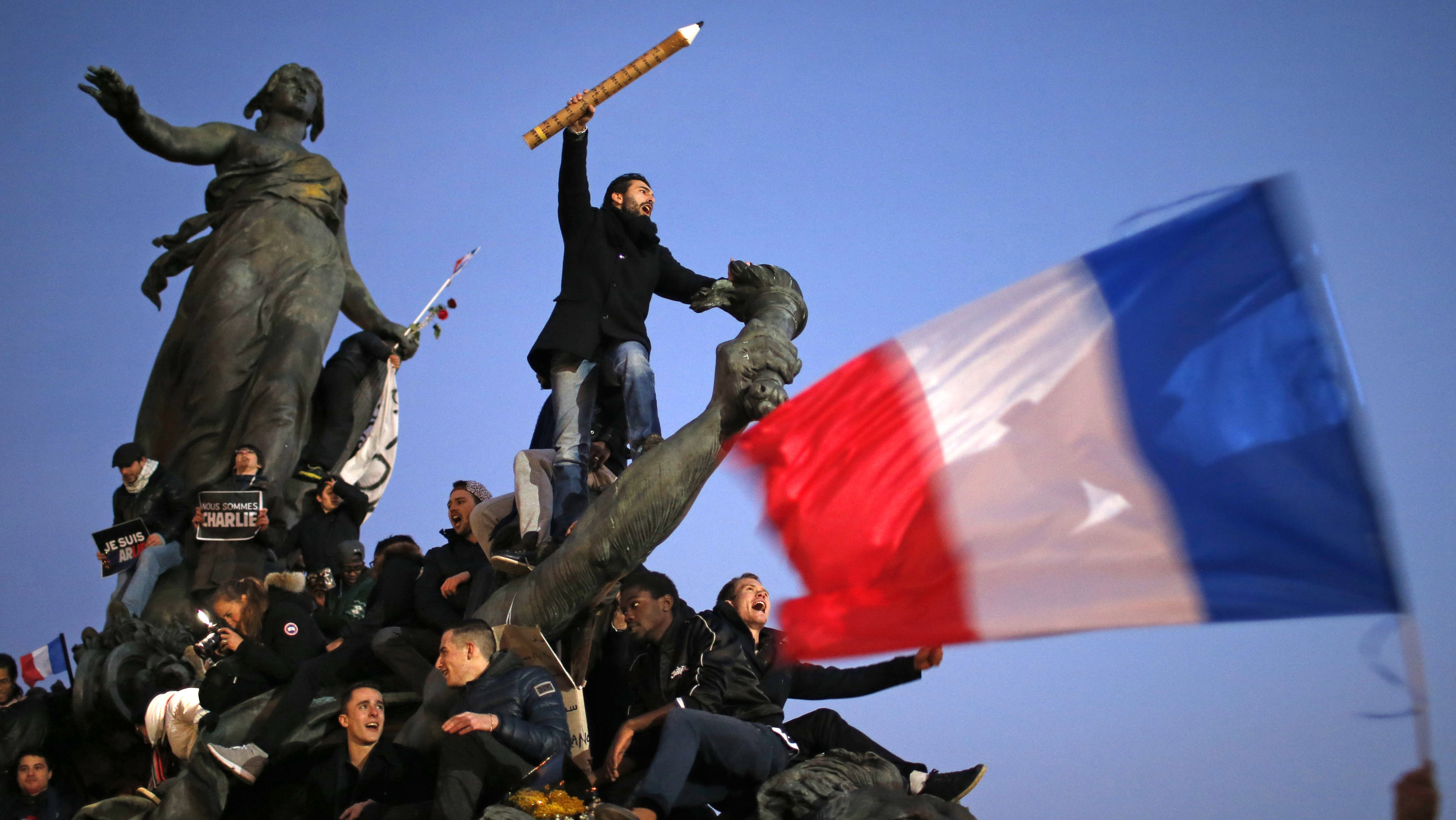 A man holds a giant pencil as he takes part in a Hundreds of thousands of French citizens solidarity march (Marche Republicaine) in the streets of Paris January 11, 2015. French citizens will be joined by dozens of foreign leaders, among them Arab and Muslim representatives, in a march on Sunday in an unprecedented tribute to this week's victims following the shootings by gunmen at the offices of the satirical weekly newspaper Charlie Hebdo, the killing of a police woman in Montrouge, and the hostage taking at a kosher supermarket at the Porte de Vincennes.