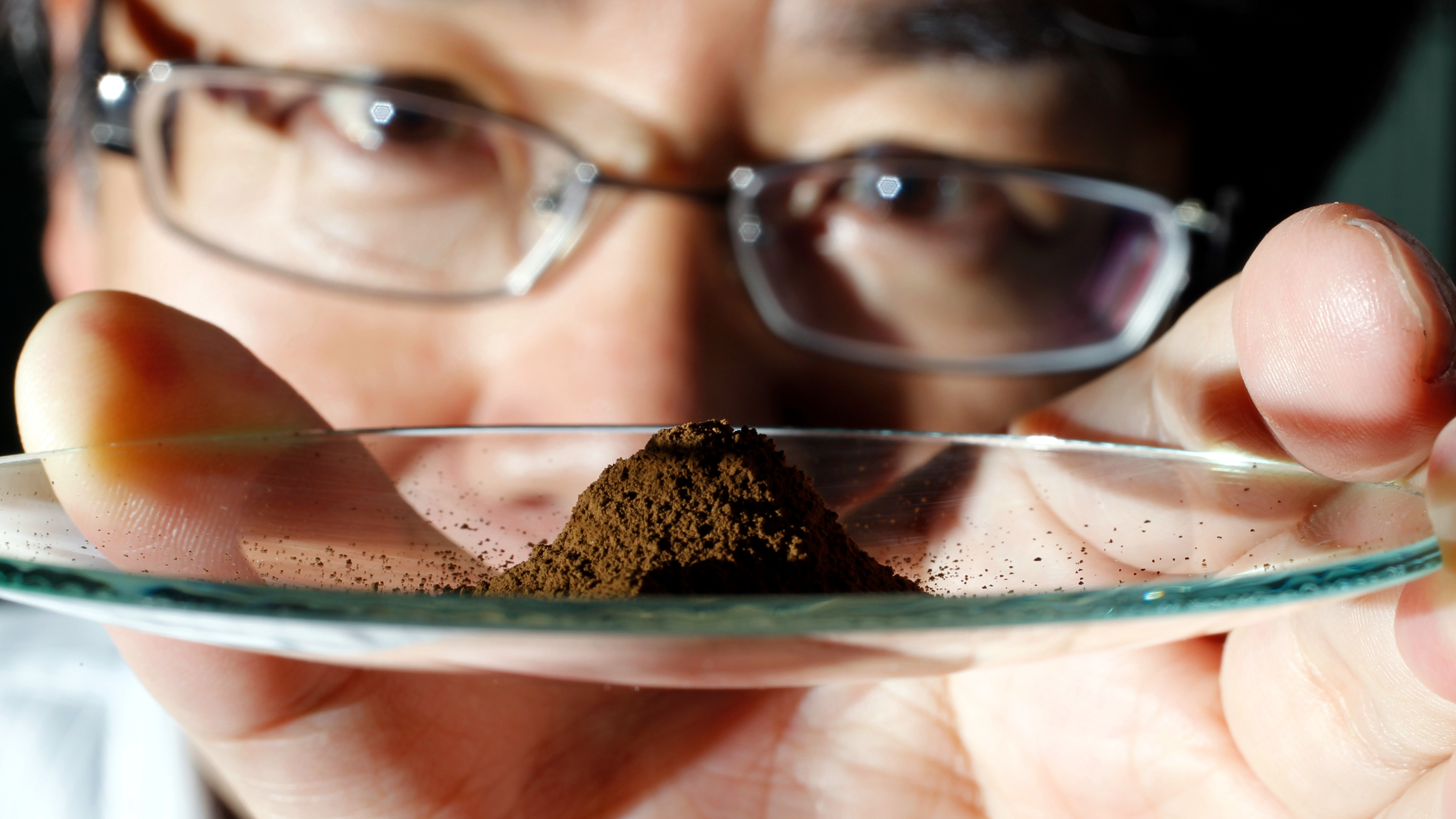 Yasuhiro Kato, an associate professor of earth science at the University of Tokyo, displays a mud sample extracted from the depths of about 4,000 metres (13,123 ft) below the Pacific ocean surface where rare earth elements were found, at his laboratory in Tokyo July 5, 2011. Vast deposits of rare earth minerals, crucial in making high-tech electronics products, have been found on the floor of the Pacific Ocean and can be readily extracted, Japanese scientists said on Monday.