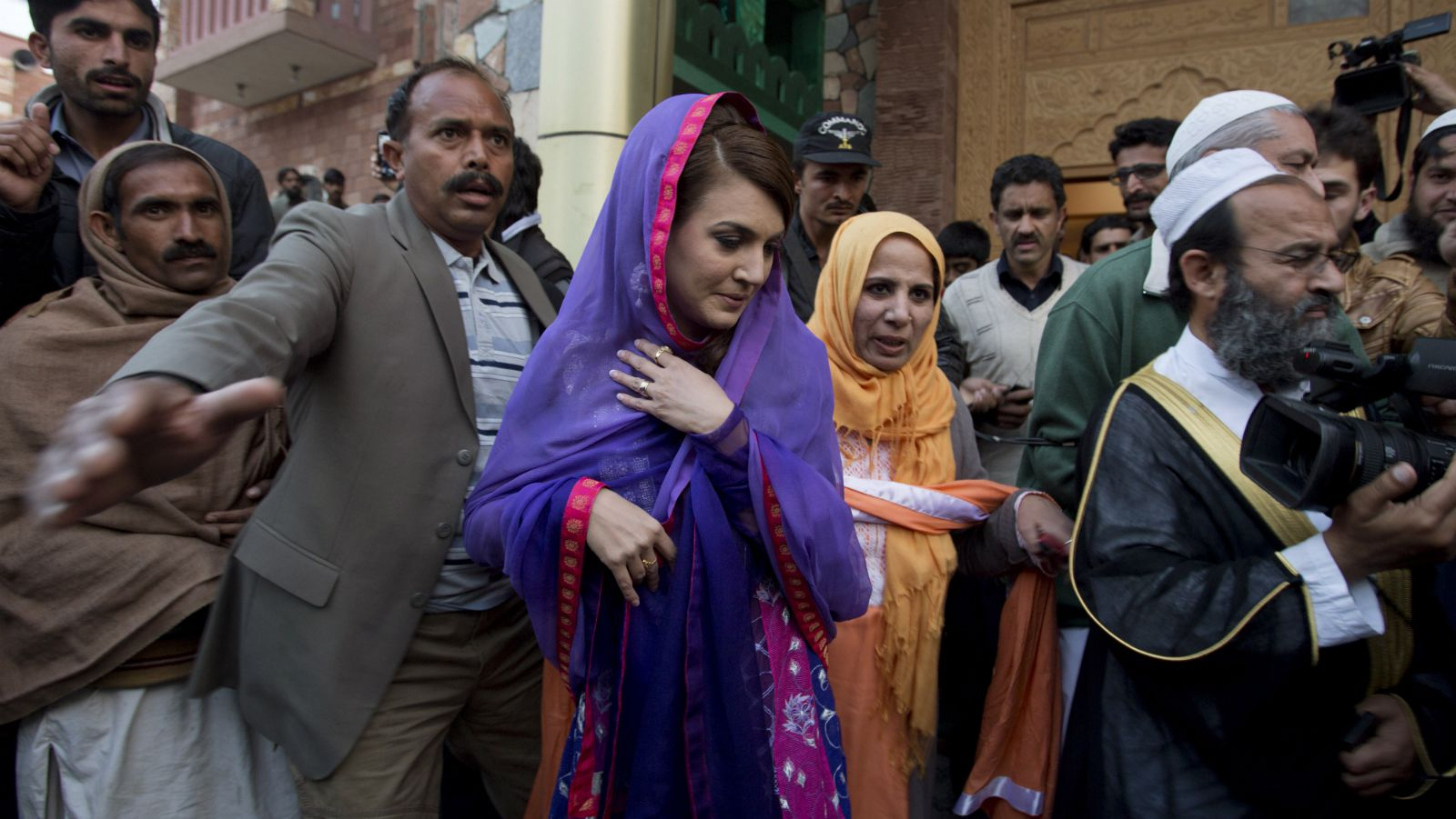 Reham Khan, center, wife of Pakistan's cricketer-turned-politician Imran Khan, leaves a local madrassa, or seminary, in Islamabad, Pakistan, Friday, Jan. 9, 2015. Imran, Pakistan's legendary cricket star and politician, tied the knot with Reham, a former journalist, Thursday, ending weeks of speculation about whether one of the country's most famous bachelors was getting married for a second time.