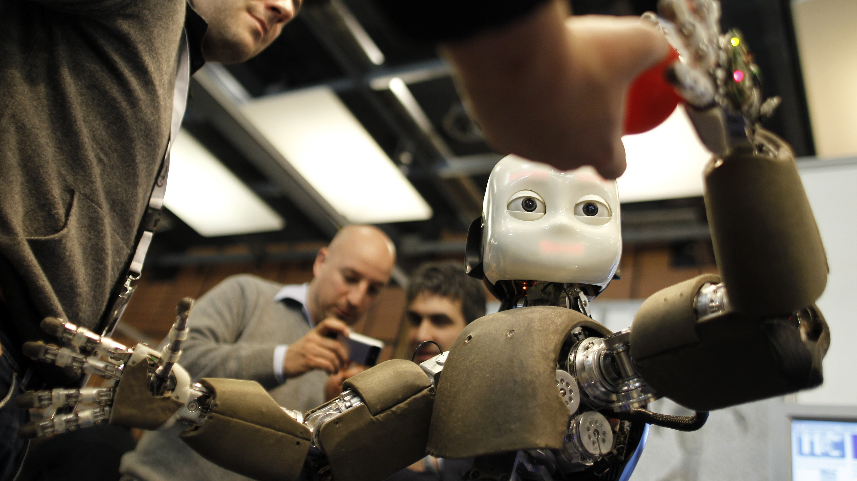 People look at the iCub robot during the Innorobo European summit, an event dedicated to the service robotics industry, in Lyon, central France, Thursday, March 15, 2012. The iCub robot, created by the Italian Institute of Technology, is used for research into human cognition and artificial intelligence. (AP Photo/Laurent Cipriani)
