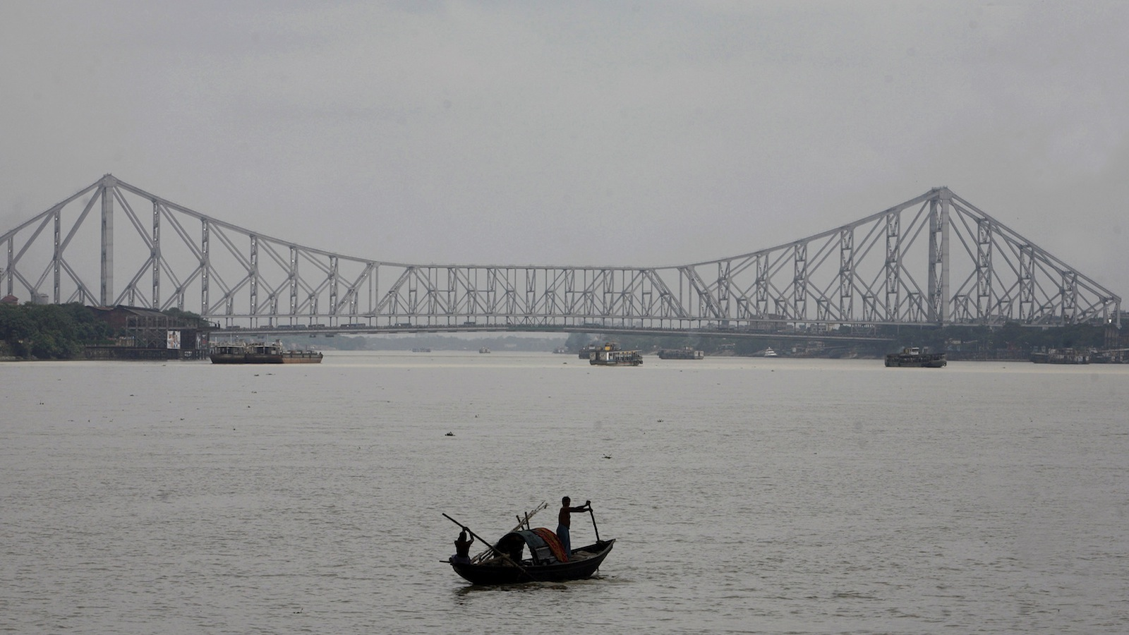 Fishermen row a boat on the Hooghly River against the backdrop of Howrah bridge in the eastern Indian city of Kolkata September 17, 2007. REUTERS/Parth Sanyal
